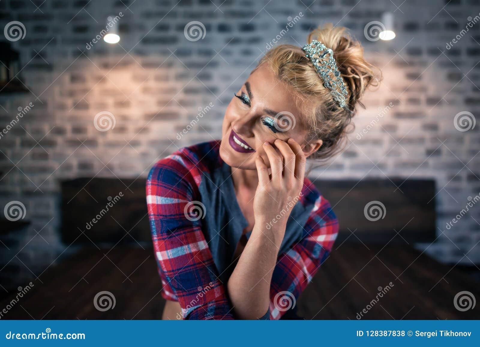 La mujer bastante joven se sienta en la cama en dormitorio elegante Muchacha rubia rusa