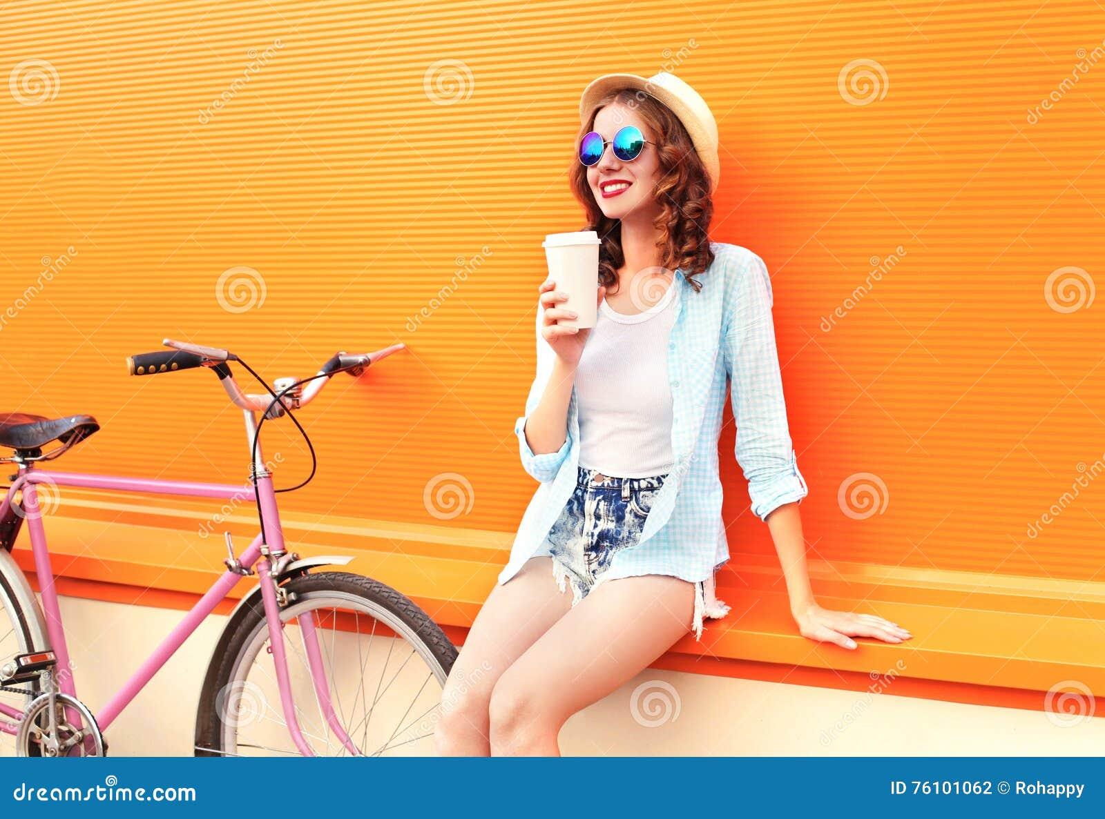 La mujer bonita de la moda bebe el café de la taza cerca de la bicicleta retra del rosa del vintage sobre naranja colorida