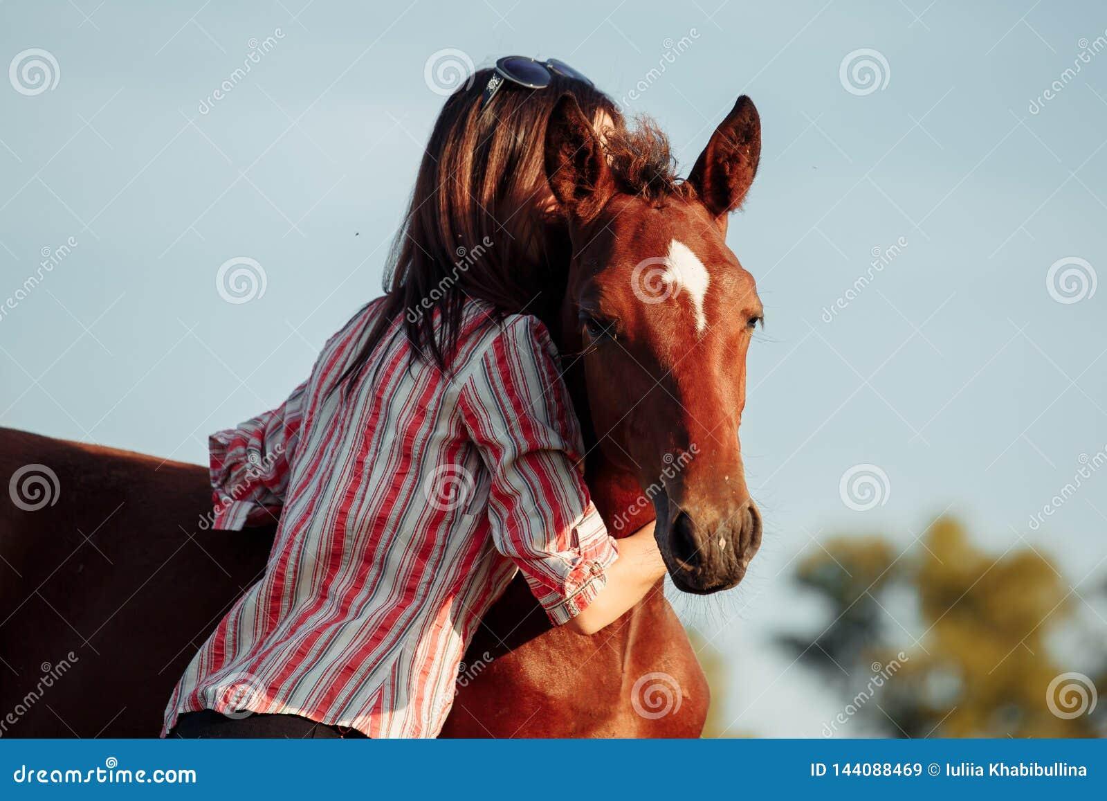 La mujer bonita joven abraza un potro en un campo Adultos jovenes