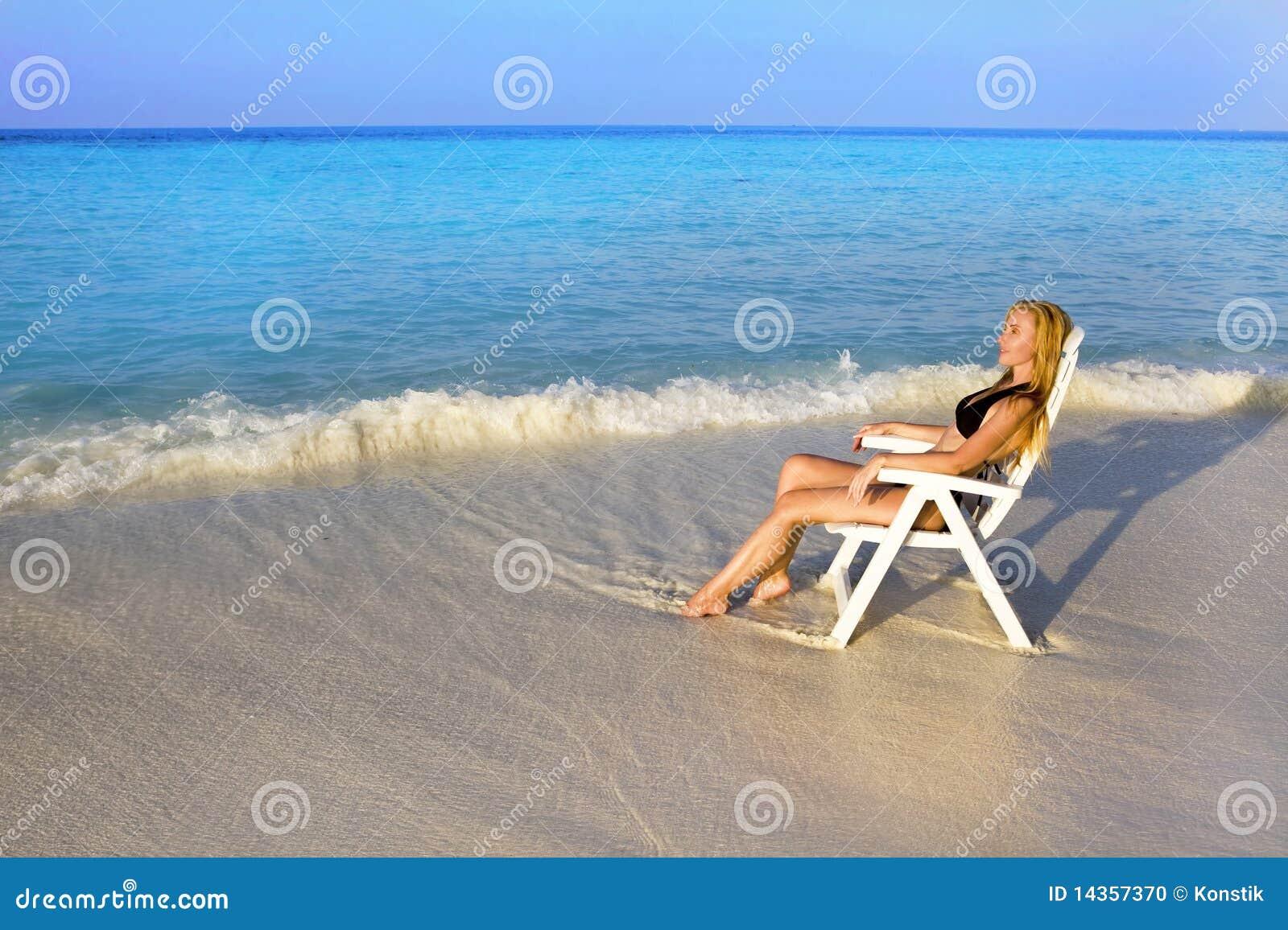 La mujer bonita joven broncea en silla de playa en el océano