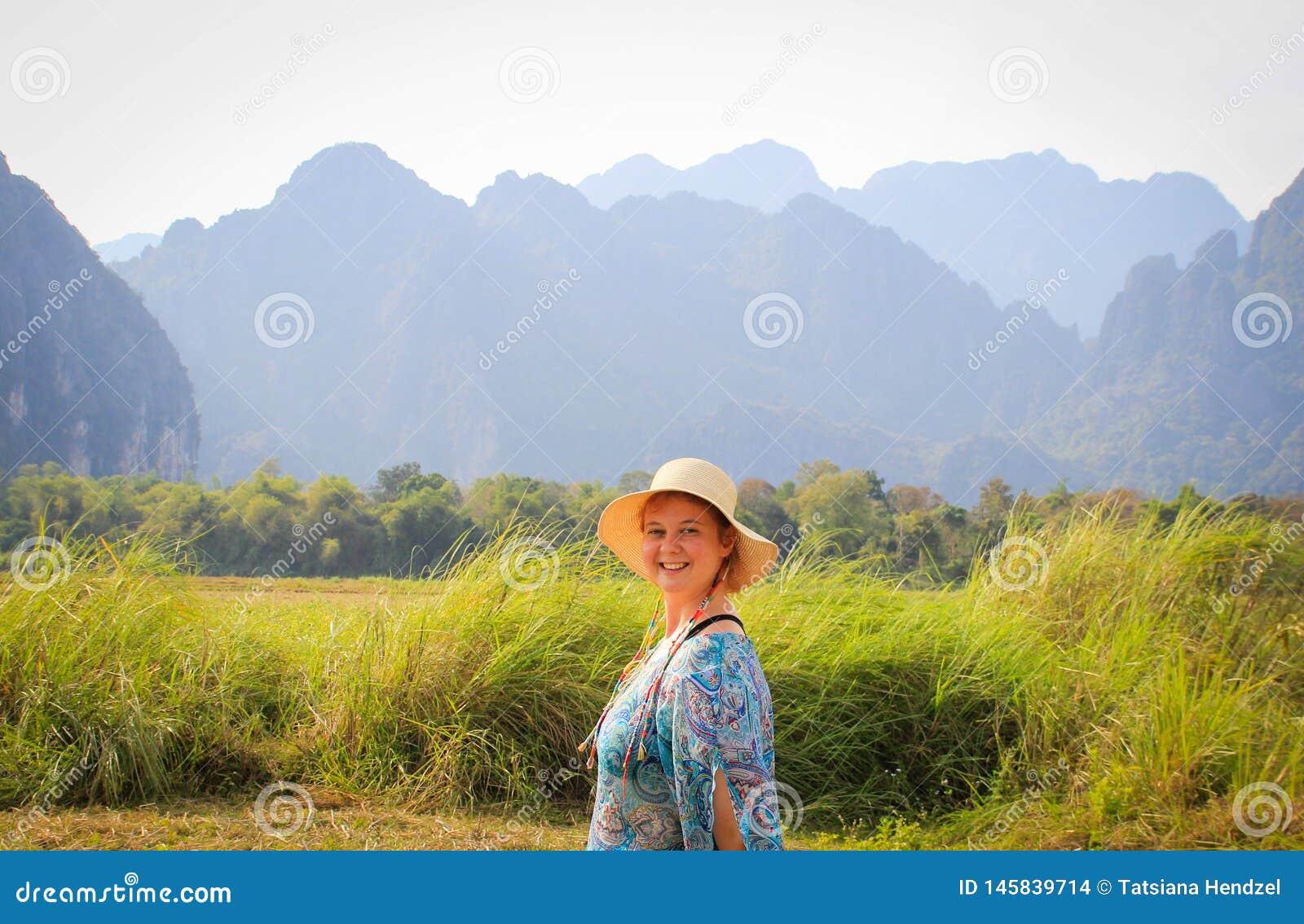 La mujer bonita joven en sombrero y vestido azul está sonriendo en la salida del sol contra la perspectiva de las montañas hermos