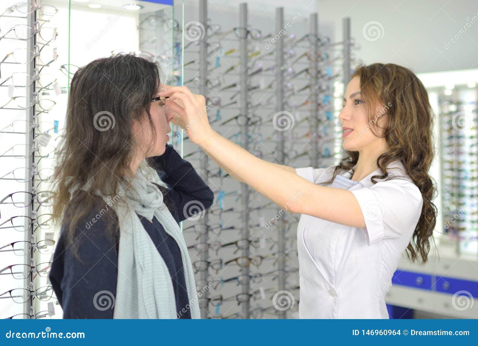 La mujer bonita joven est? intentando los vidrios del ojo encendido en una tienda de las gafas con ayuda de un ayudante y de las