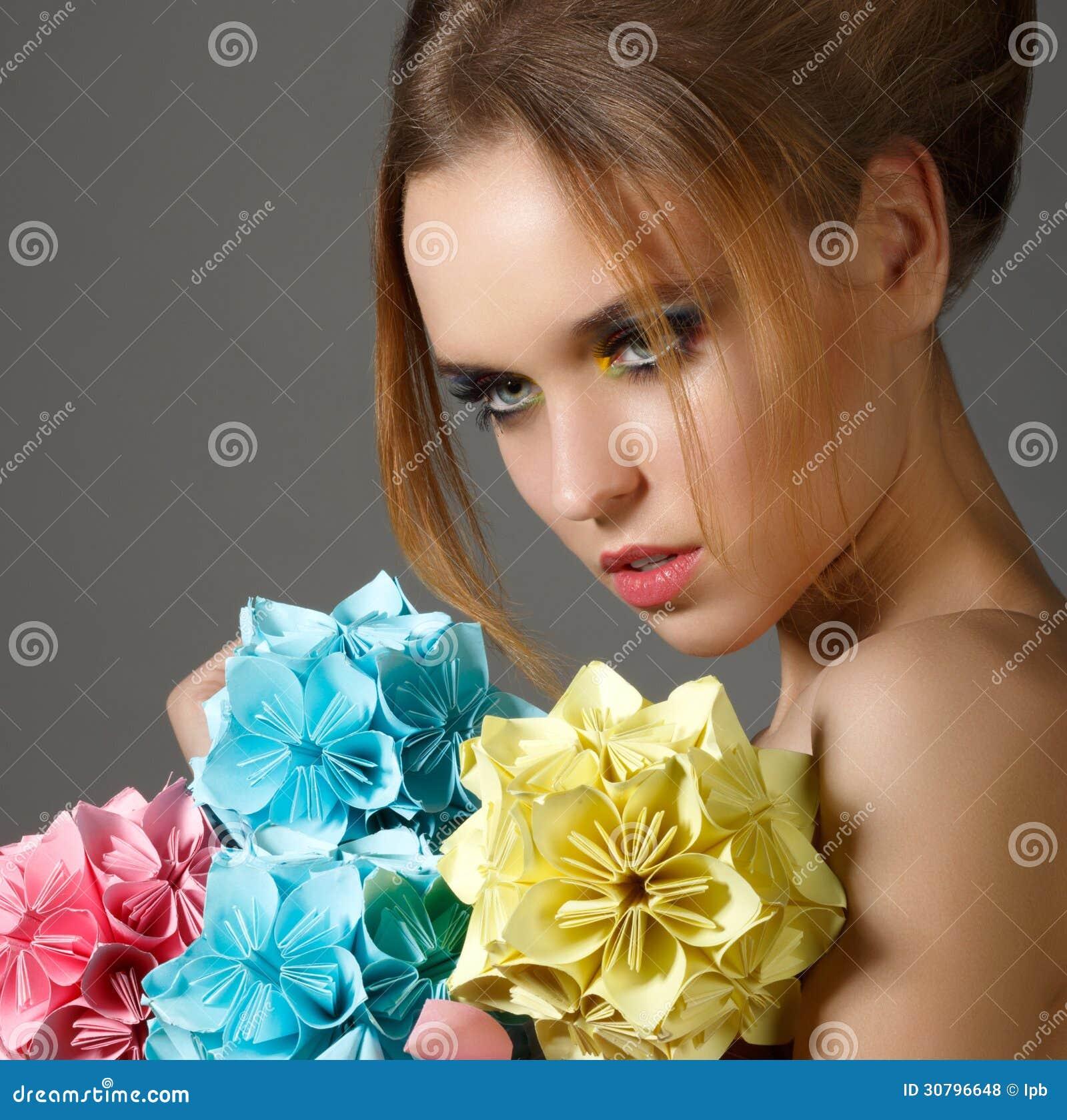 La mujer brillante hermosa que sostiene el ramo de papiroflexia de papel florece