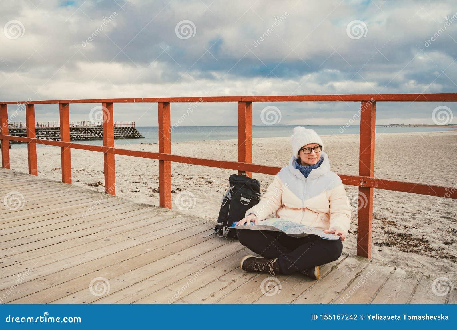 La mujer caucásica en sombrero y chaqueta con la mochila en invierno se sienta en el embarcadero de madera en la playa cerca de M