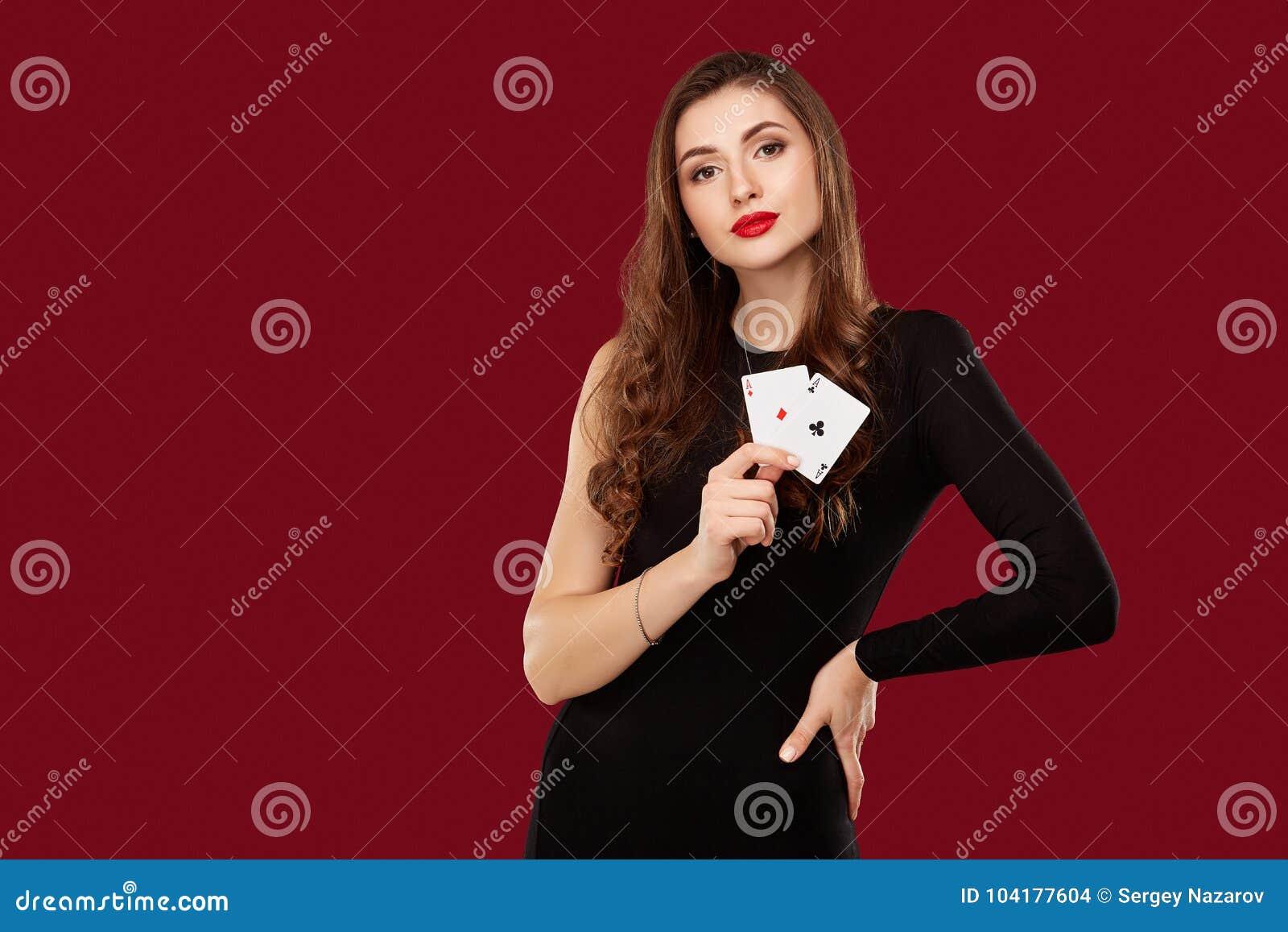 La mujer caucásica hermosa en vestido negro con el póker carda el juego en casino