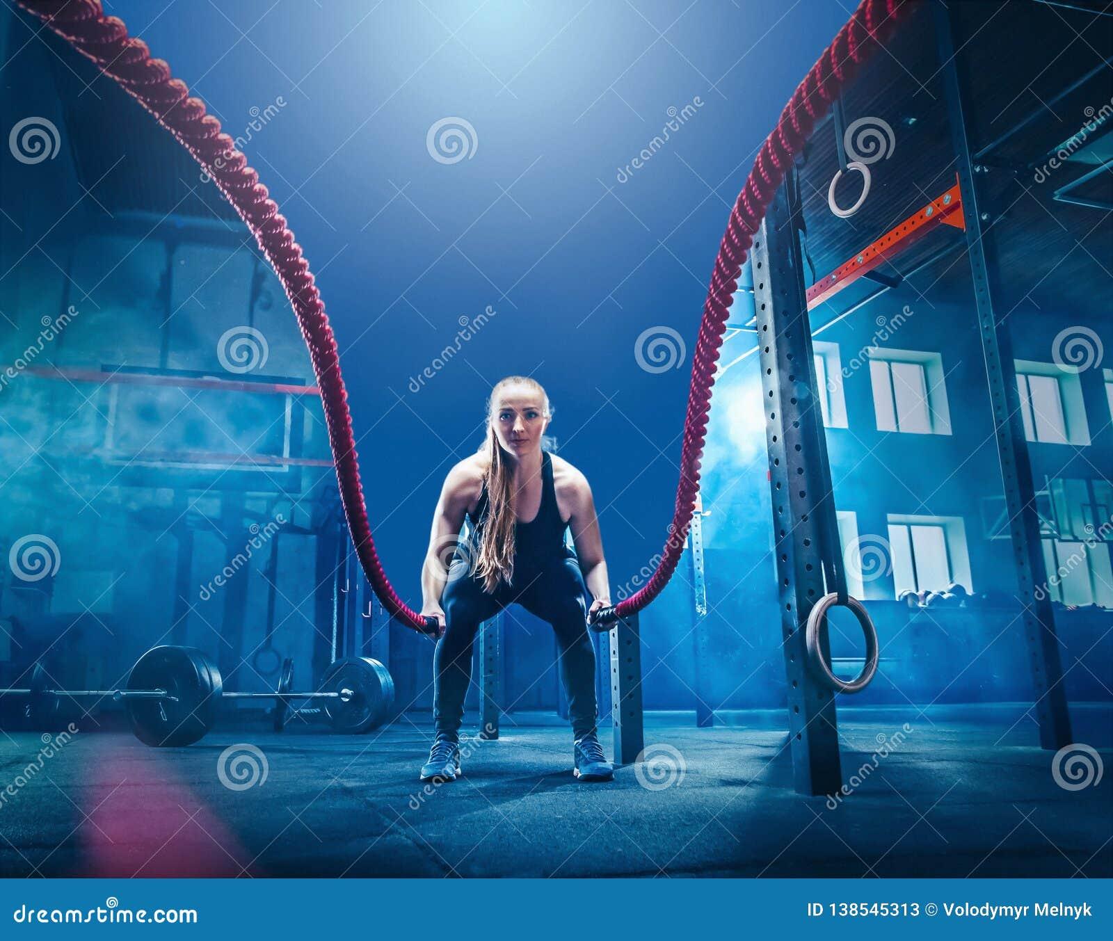 La mujer con batalla de la cuerda de la batalla ropes ejercicio en el gimnasio de la aptitud