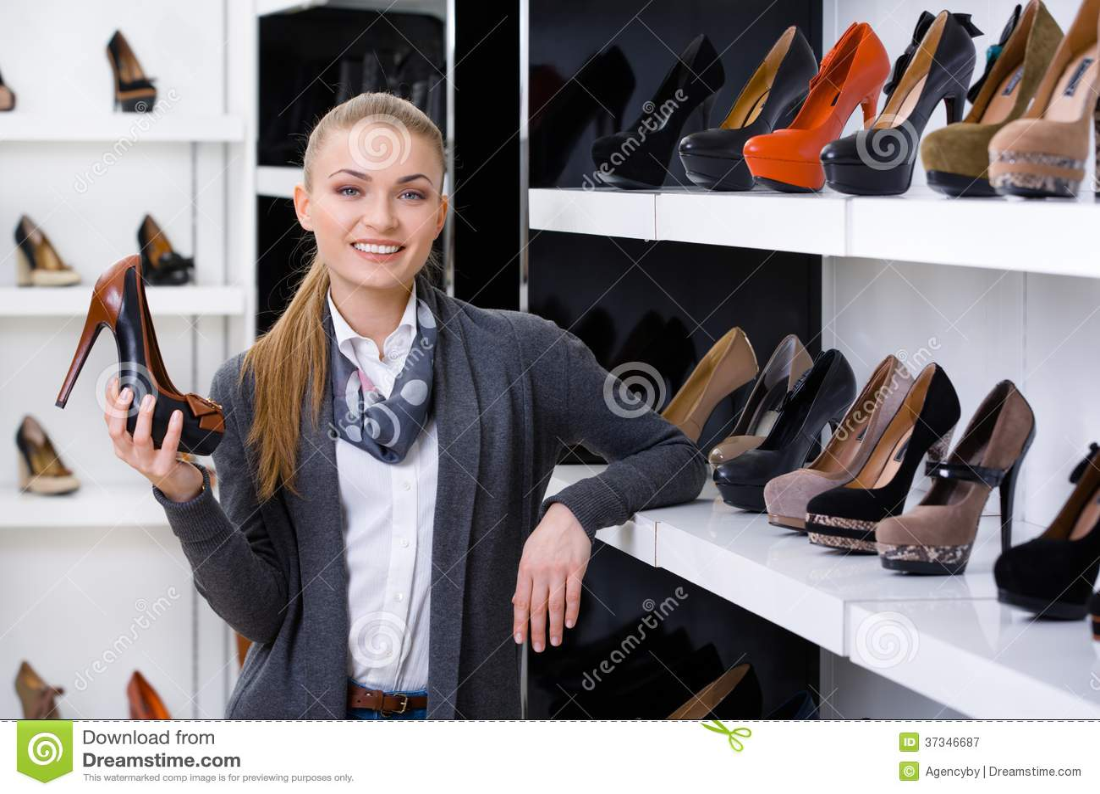 La mujer con el zapato a disposición elige los zapatos de tacón alto