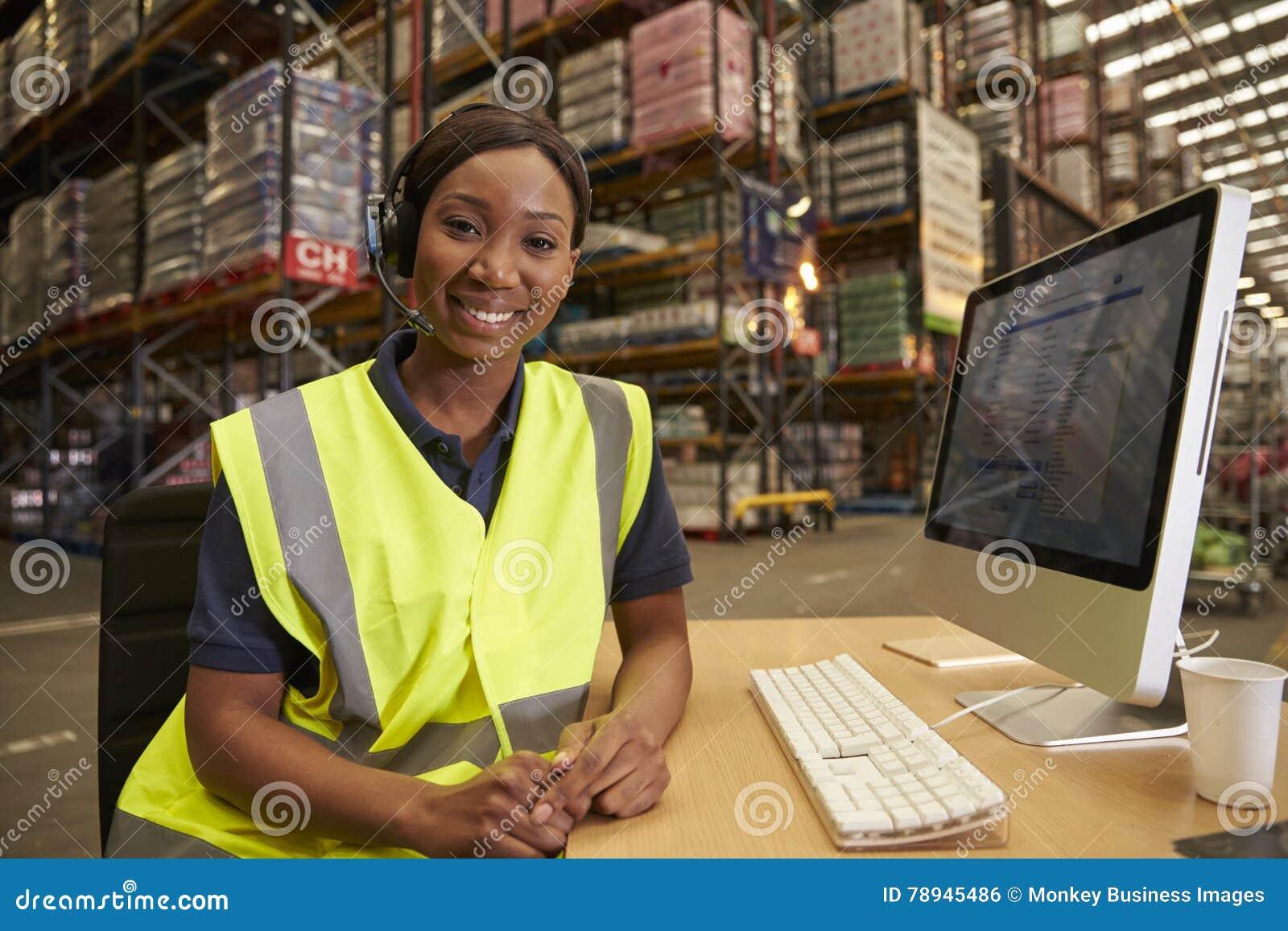 La mujer con las auriculares en una oficina del almacén mira a la cámara