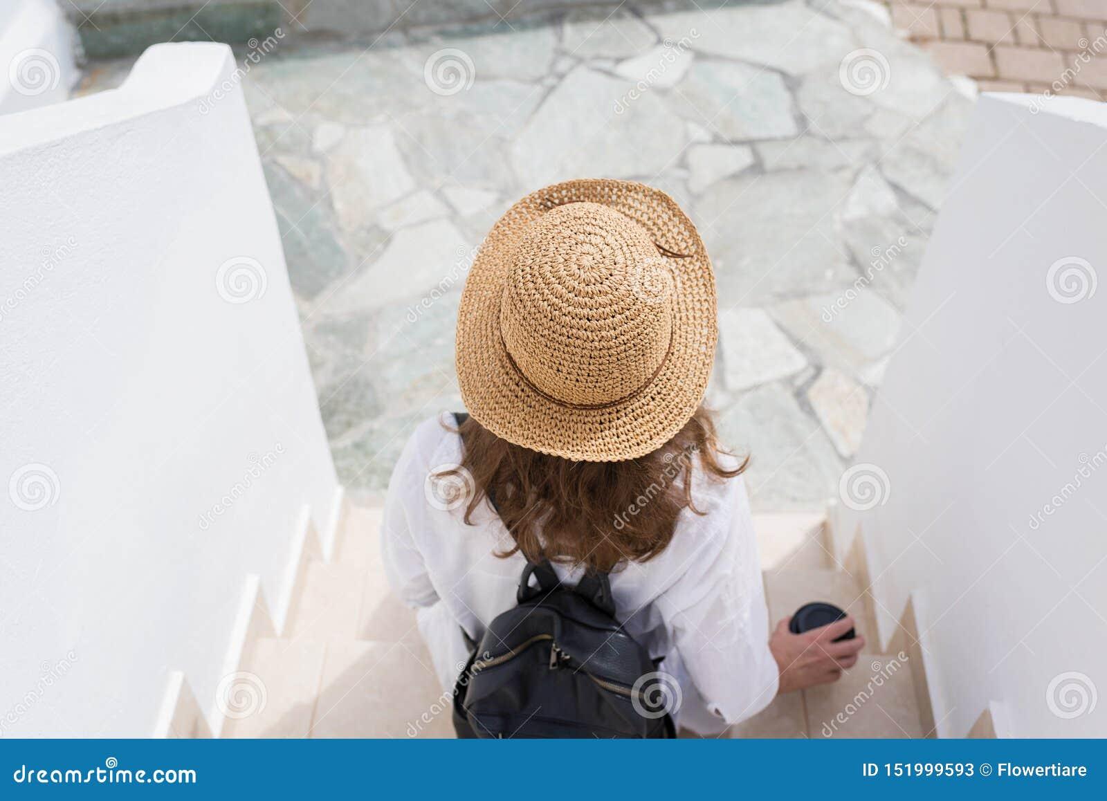 La mujer con la mochila en un sombrero de paja y la taza de café de papel se sienta en los pasos y se relaja de la ciudad de vaca