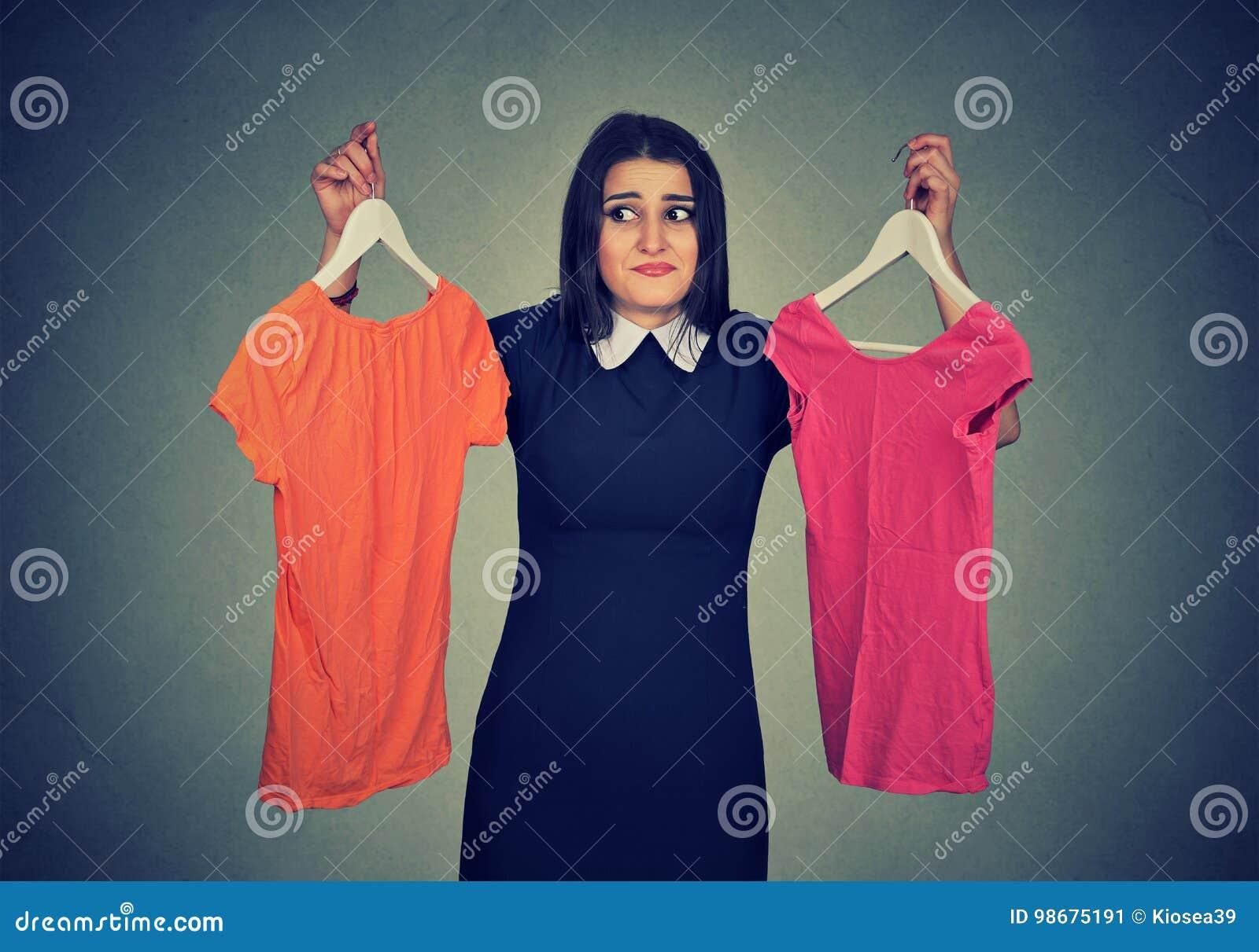 La mujer confusa que elige entre los vestidos y no puede tomar la decisión