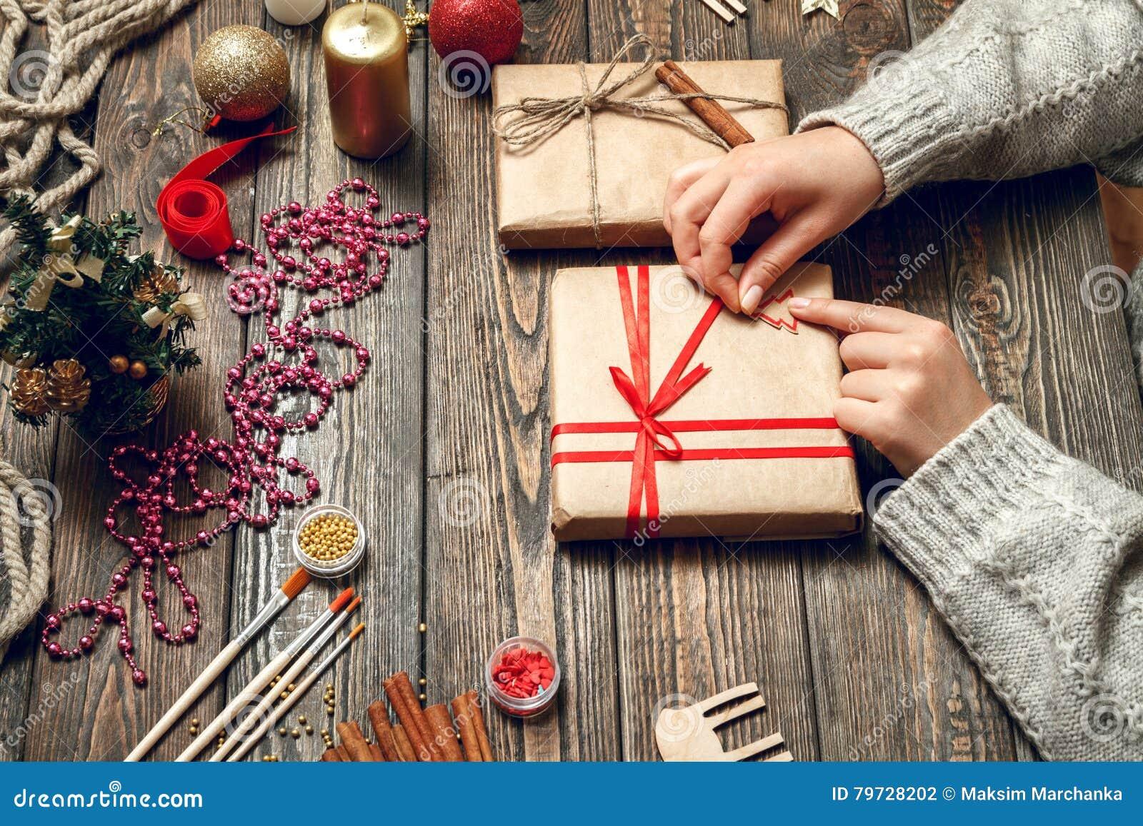 La mujer crea los regalos elegantes de la Navidad