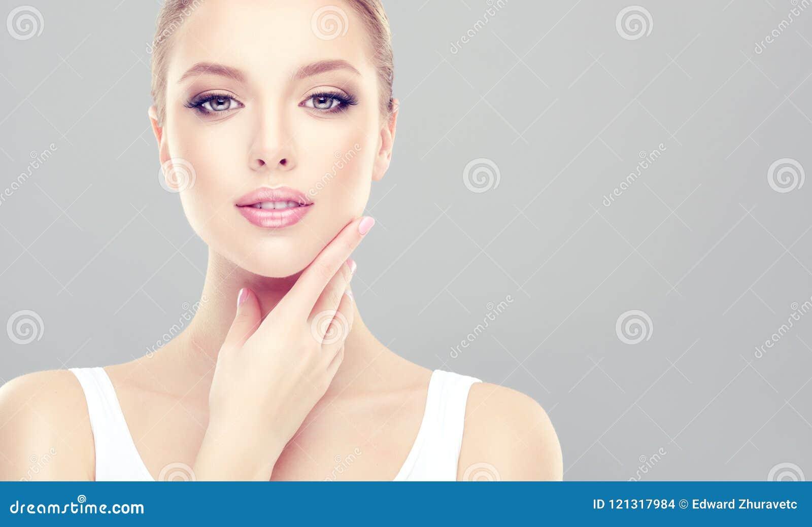 La mujer de fascinación con la piel fresca limpia está tocando la cara blando