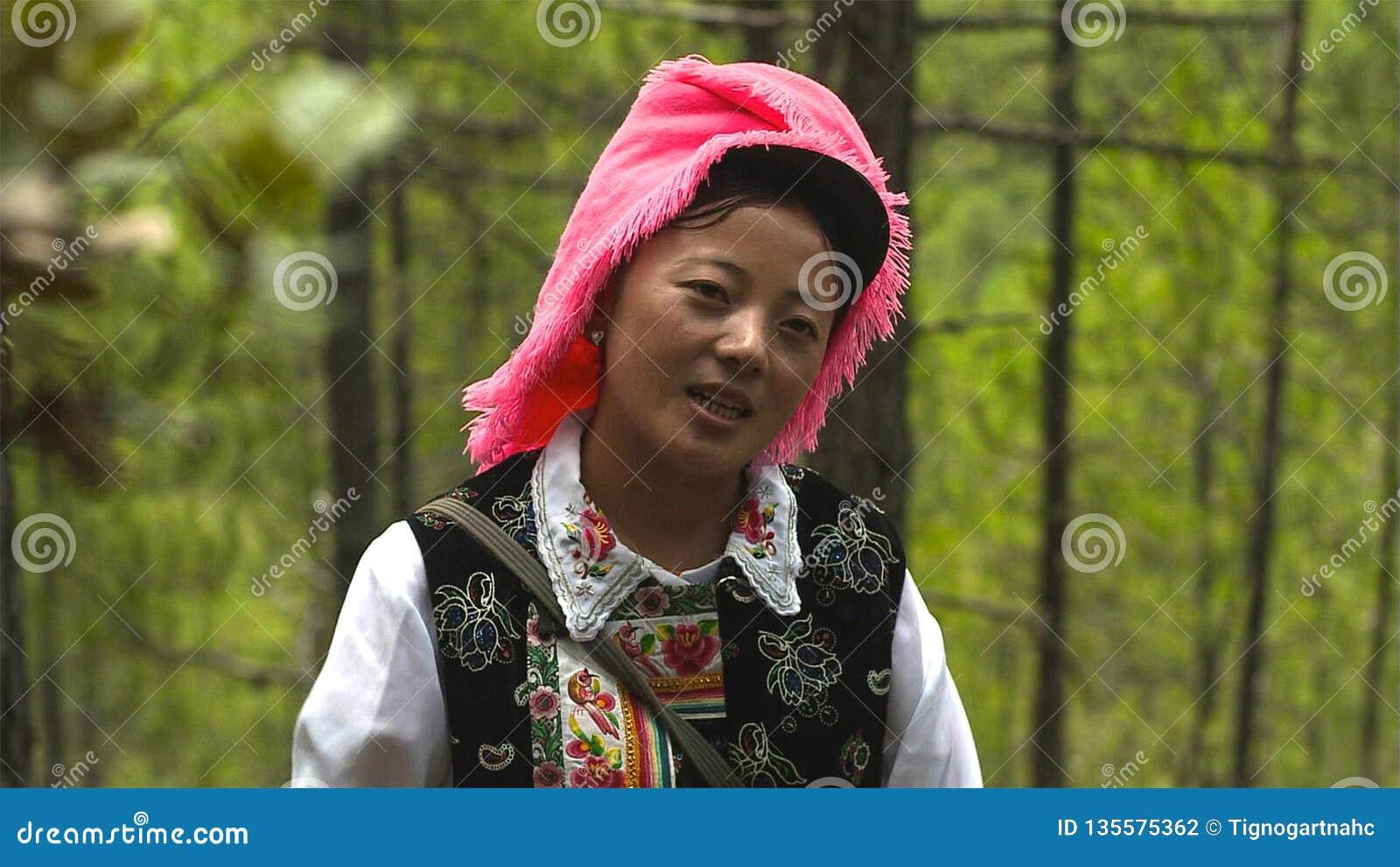 La mujer de los tibetanos en el pueblo de Jidi, se sienta en el centro del área de la producción del matsutake en Shangri-La yunn