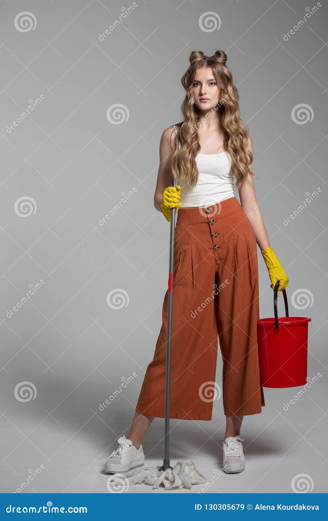 La mujer de moda con el pelo largo sostiene a disposición un cubo rojo