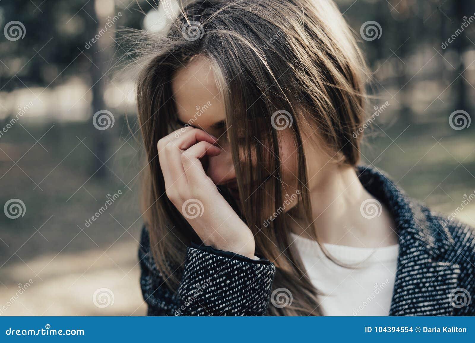 La mujer de moda tímida cubre su cara con su mano