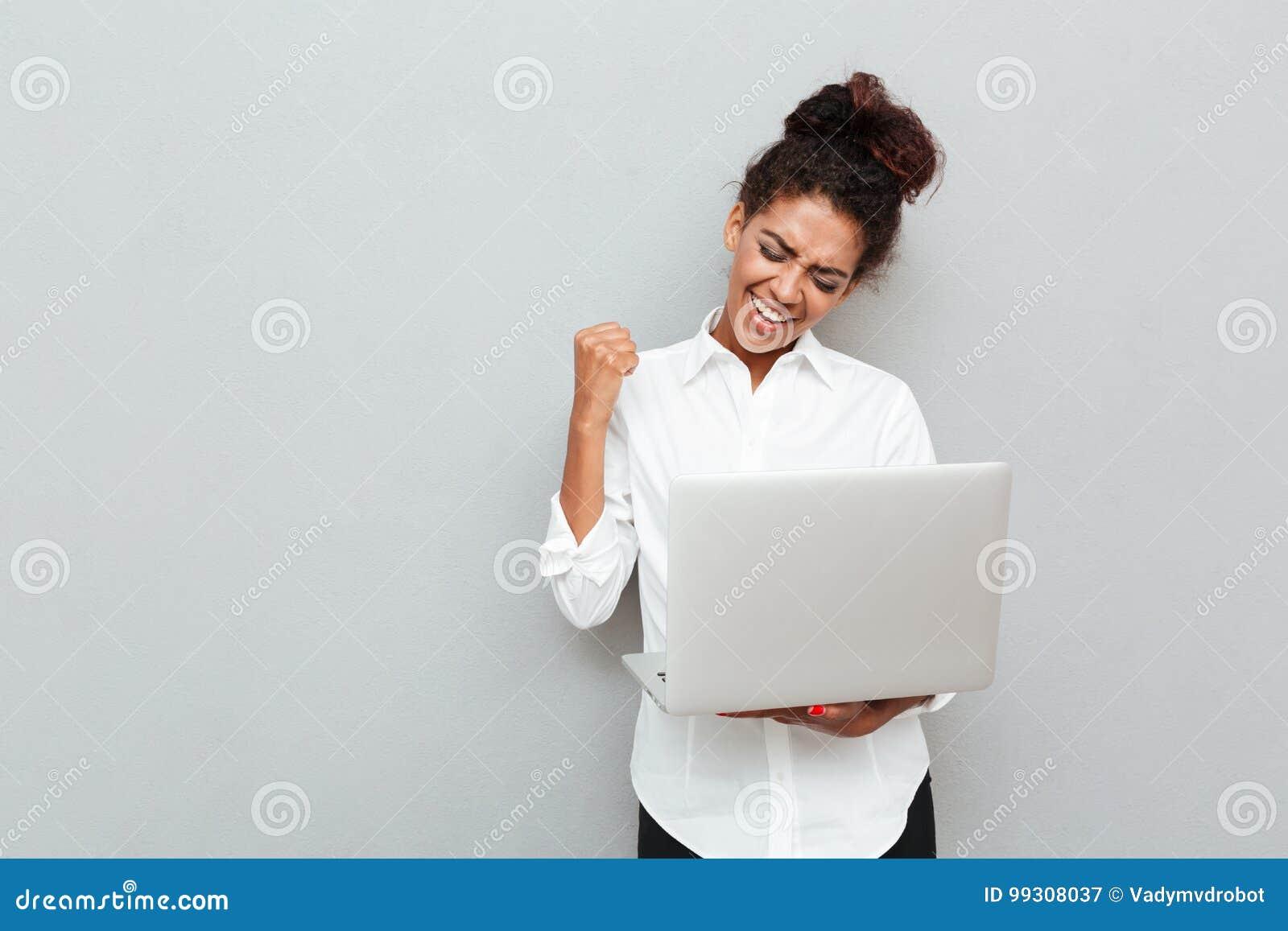La mujer de negocios alegre hace gesto del ganador