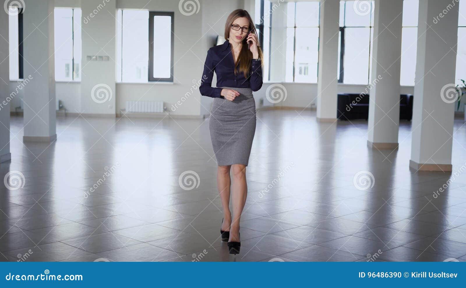 a523cc00b La mujer de negocios de pelo largo hermosa vestida en blusa azul, falda  gris y zapatos de tacón alto está caminando en la oficina.