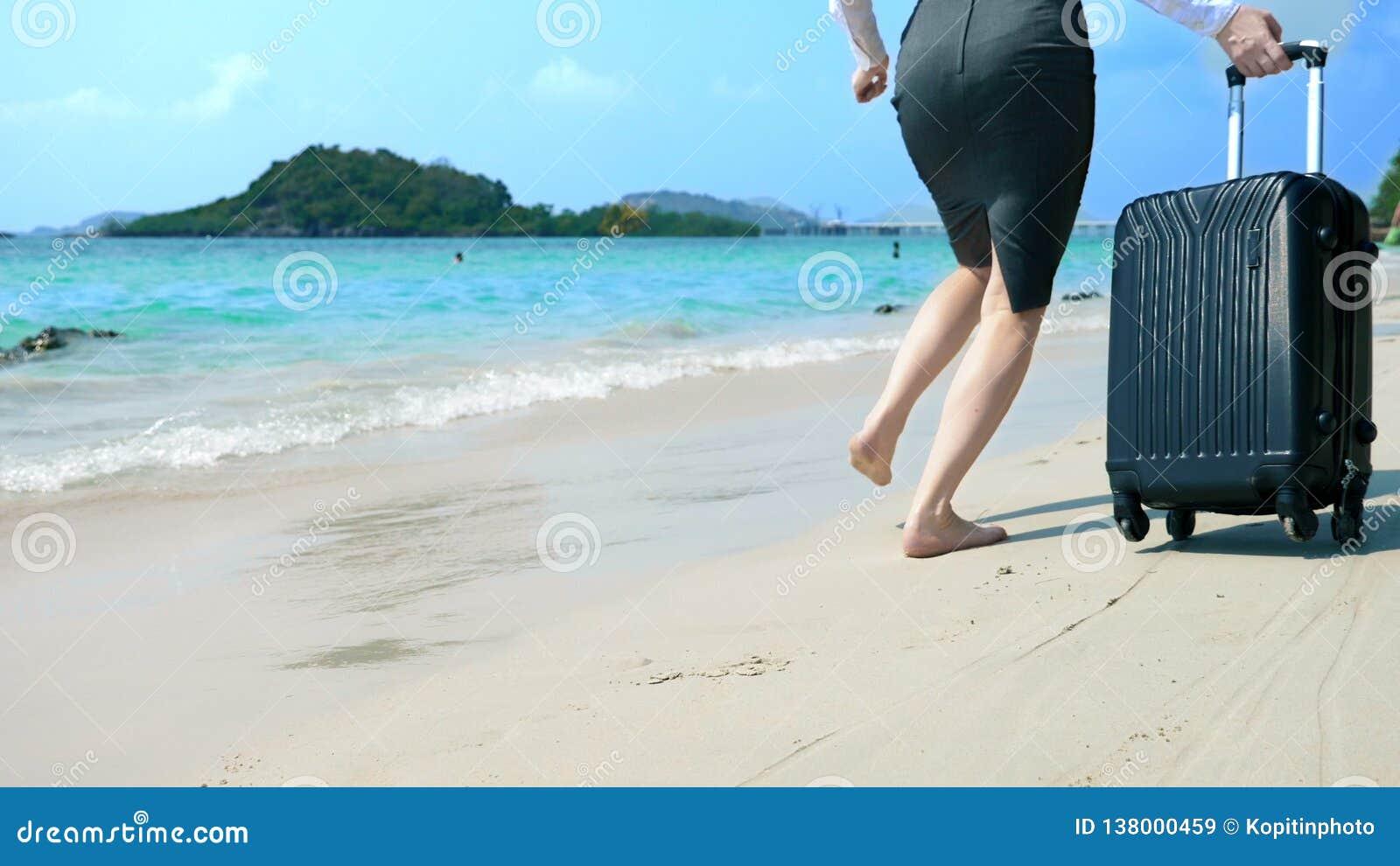 La mujer de negocios en ropa de la oficina corre descalzo al mar a lo largo de una playa arenosa blanca vacaciones independientes