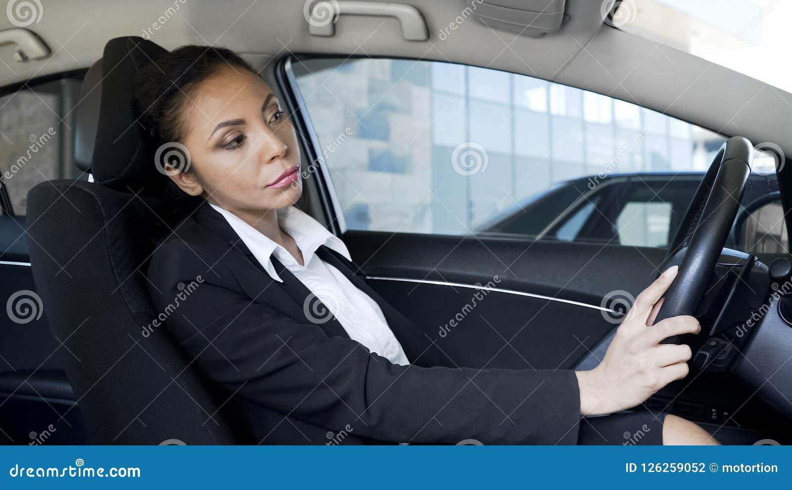 La mujer de negocios enfadada cansada se pegó en atasco, tarde para la reunión importante