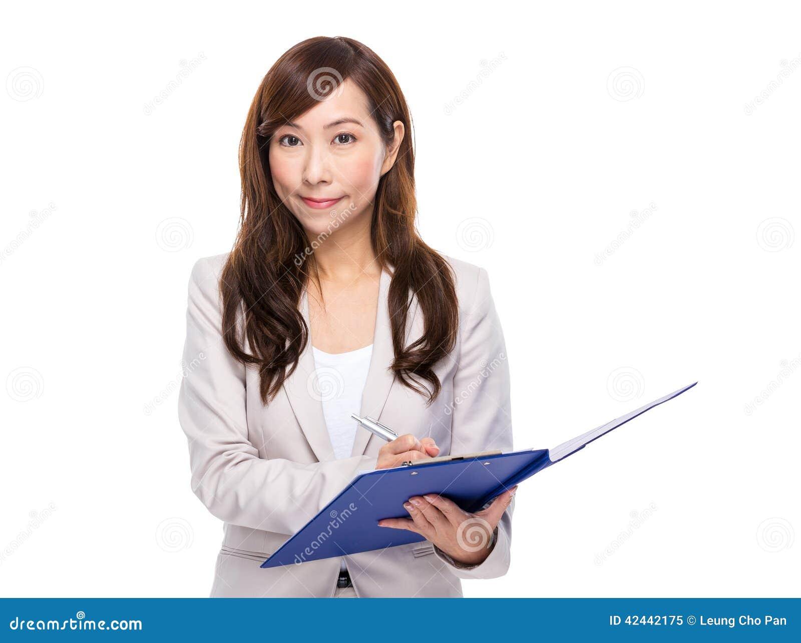 La mujer de negocios escribe algo en el cojín del fichero