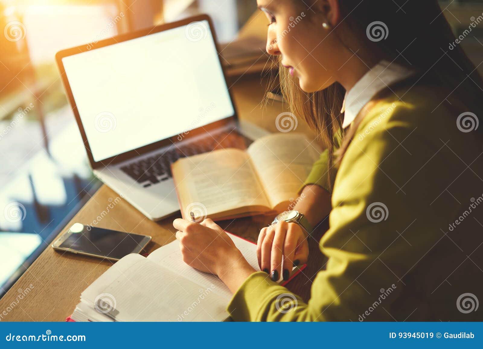 La mujer de negocios hermosa con el pelo oscuro y el suéter amarillo trabaja en coworking