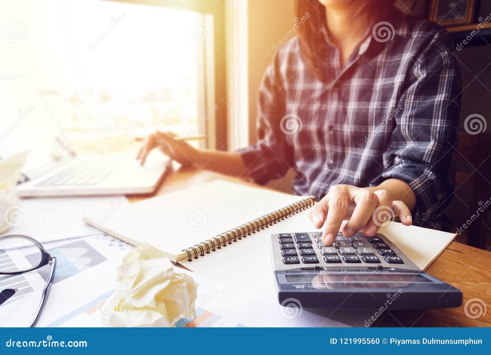 La mujer de negocios que usa la calculadora en la oficina para calcula la contabilidad