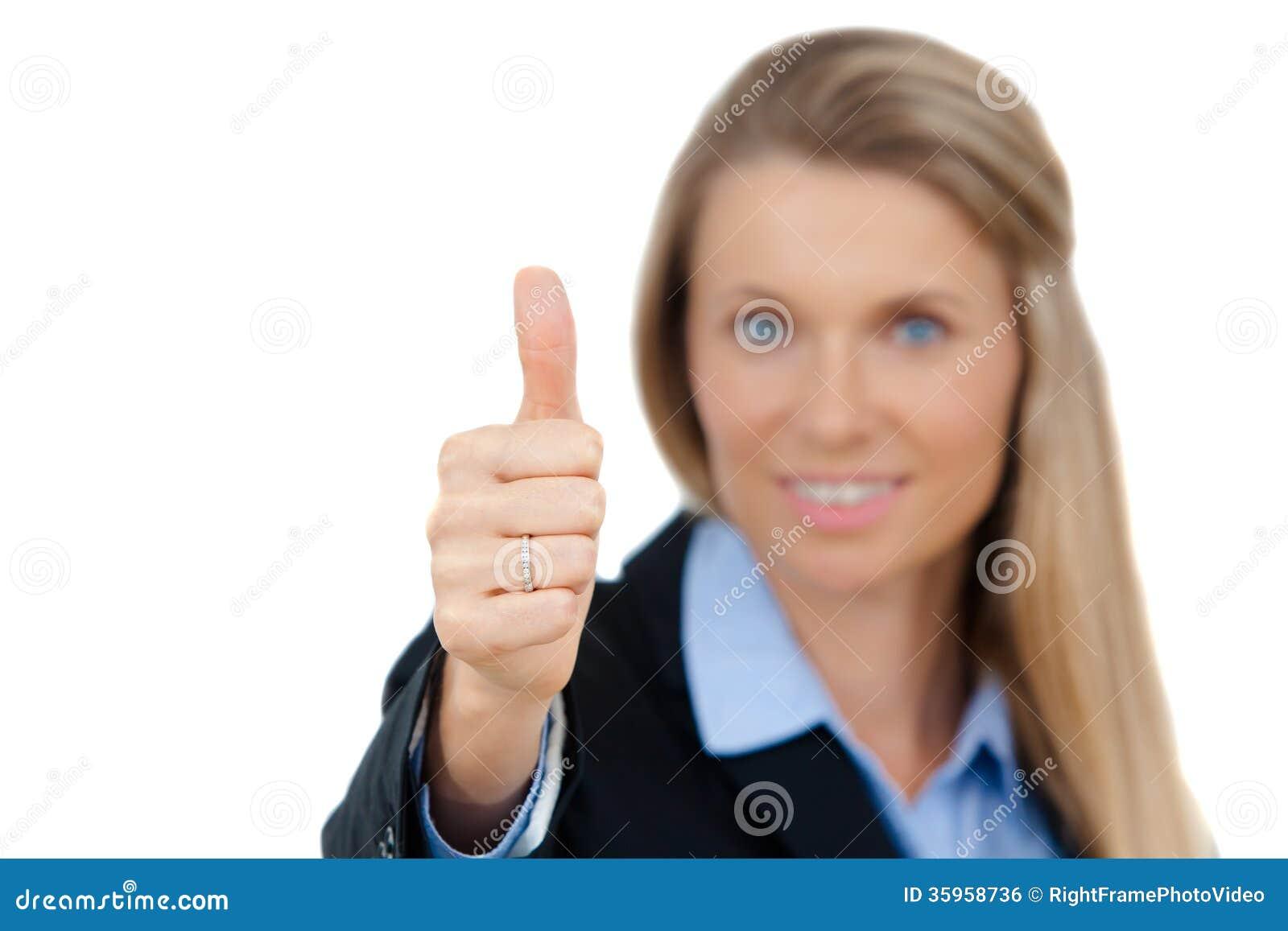 La mujer de negocios sonriente que muestra los pulgares sube la muestra