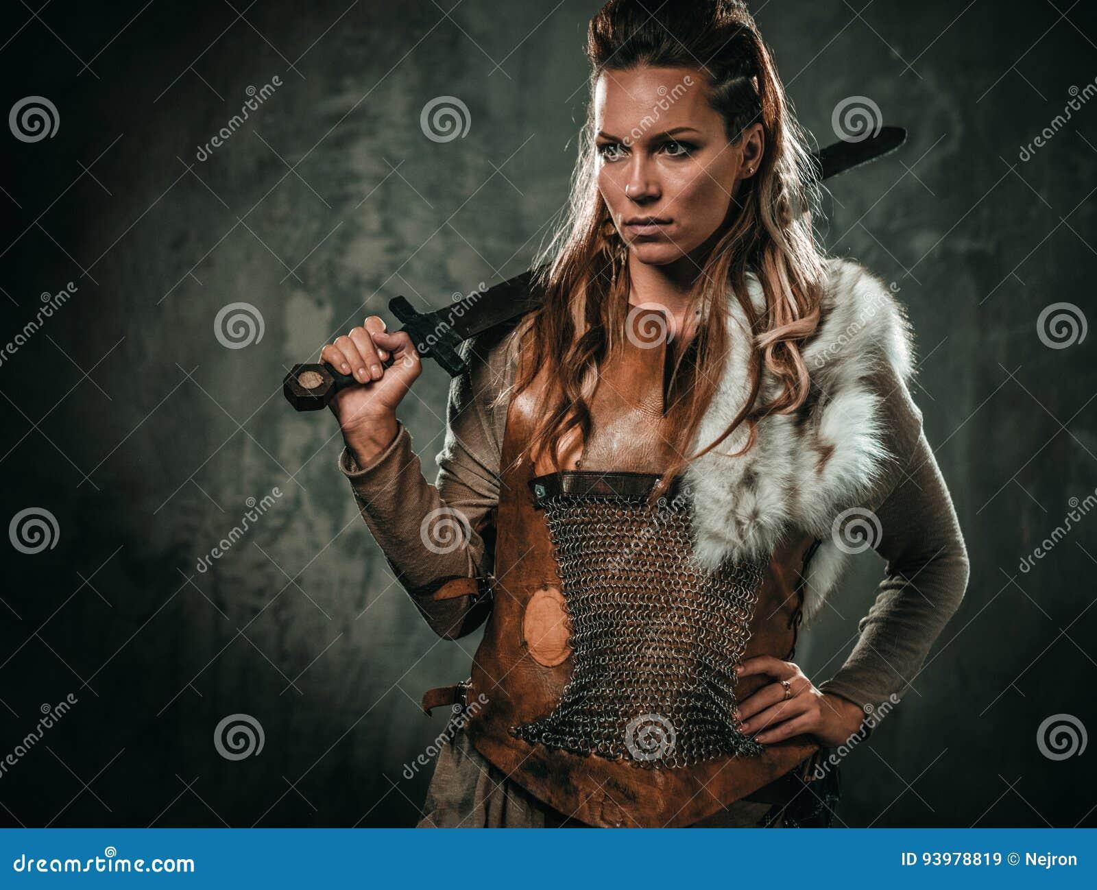 La mujer de Viking con el arma fría en un guerrero tradicional viste