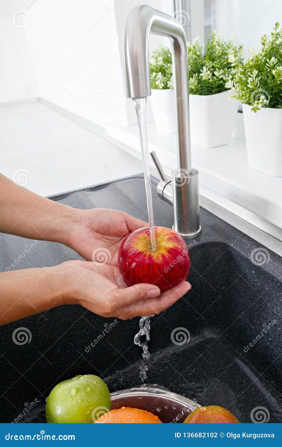 La mujer del cocinero lava una manzana debajo de la agua corriente de un golpecito de agua