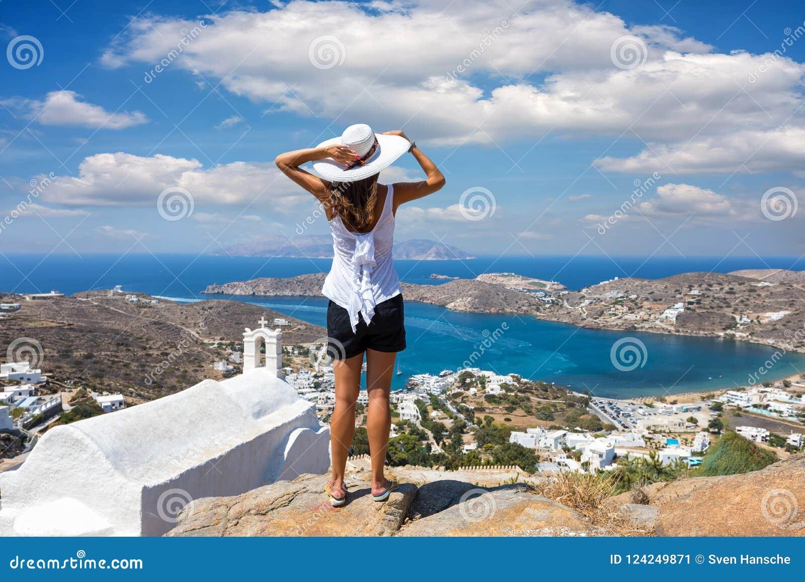 La mujer del viajero disfruta de la visión a la isla hermosa de IOS, Cícladas, Grecia