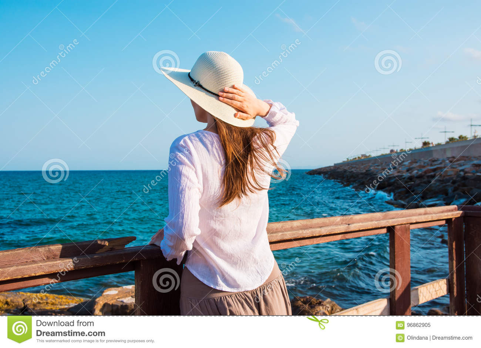 La mujer delgada hermosa joven en sunhat con el pelo largo en estilo del boho viste en la mirada de la orilla y el cielo azul del