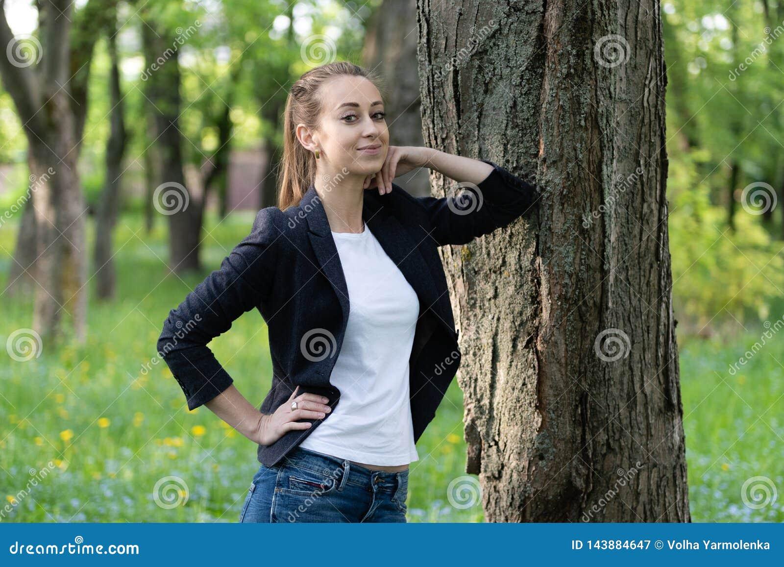 La mujer delgada joven descansa sobre un tronco de árbol, ella mira todo derecho con una mirada soñadora