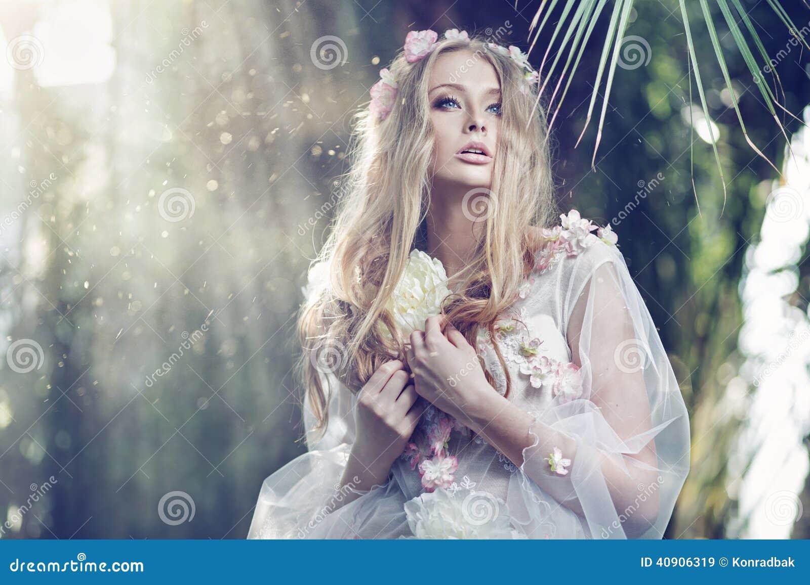 La mujer delicada magnífica con el sol emite en el fondo