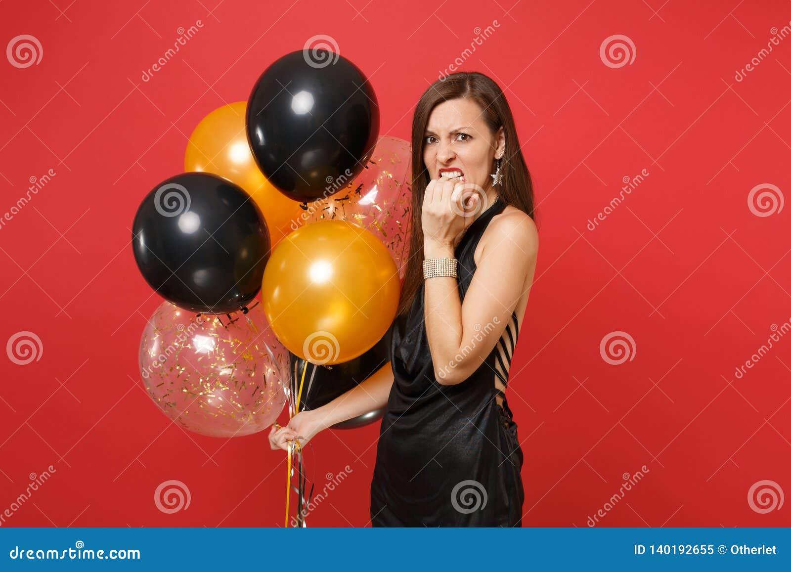 La mujer descontenta Irritated en vestido negro celebra los balones de aire del control que roe los fingeres, clavos a mano aisla