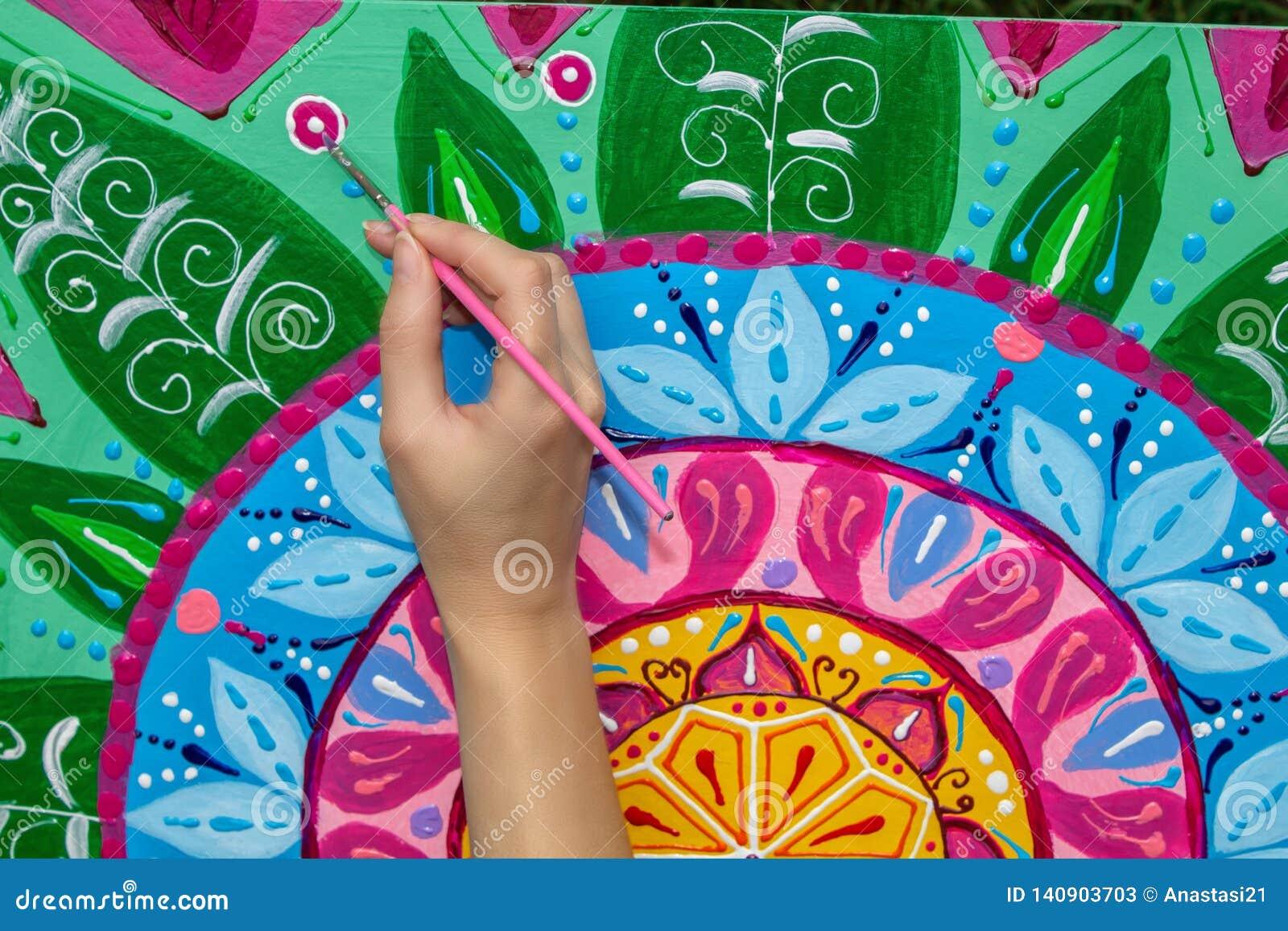 La mujer dibuja una mandala, mano con un primer del cepillo