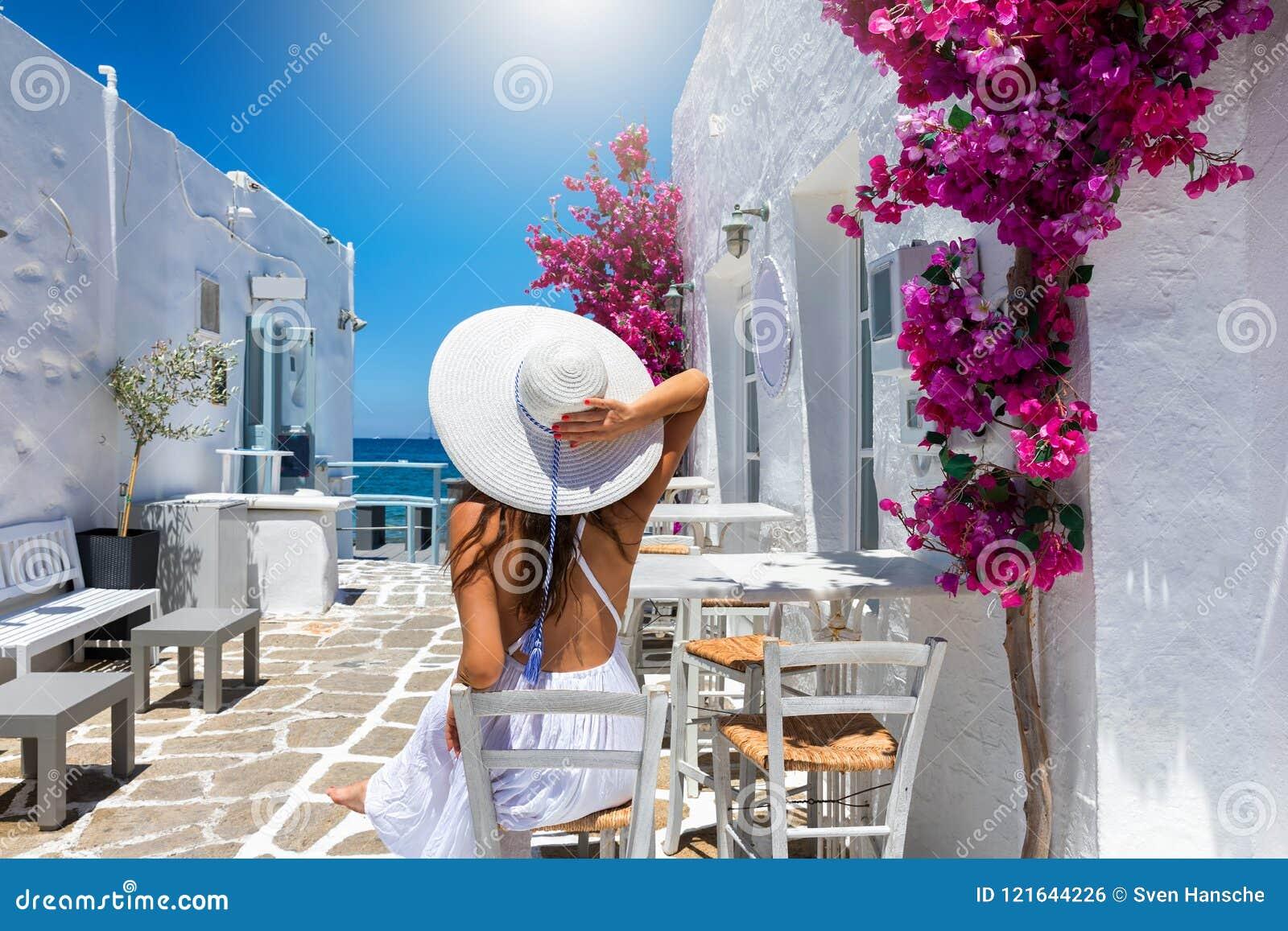 La mujer disfruta del ajuste clásico de las casas blancas y de las flores coloridas en las islas de Cícladas de Grecia