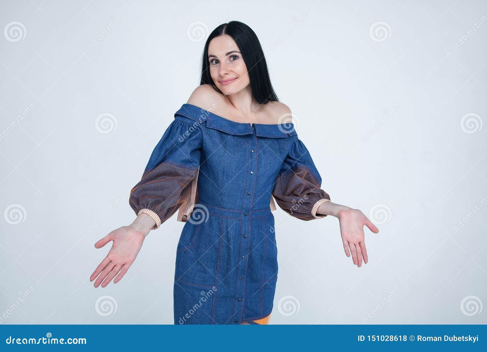 La mujer dudosa inconsciente separa las manos, aumenta las cejas con la vacilación, vestida en equipo elegante, siente desorienta