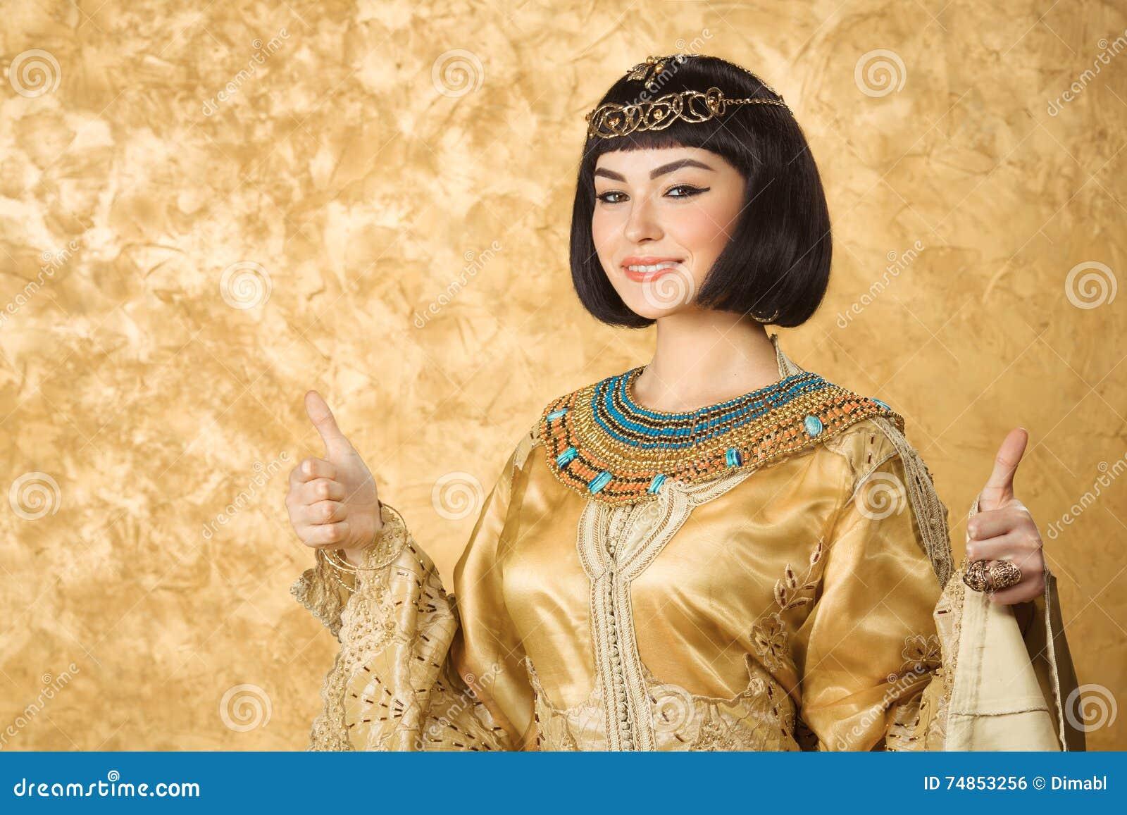 La mujer egipcia sonriente feliz le gusta Cleopatra con los pulgares encima del gesto, en fondo de oro
