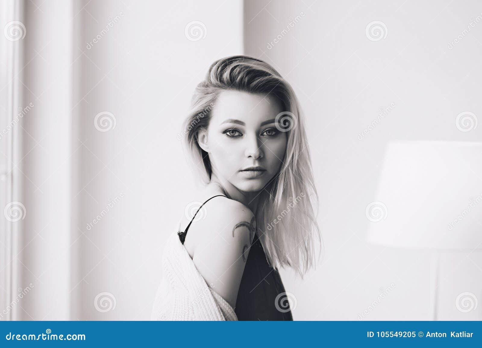 La mujer elegante blanca hermosa en interrior escandinavo acogedor se sienta en casa cerca de la ventana grande, retrato del herm