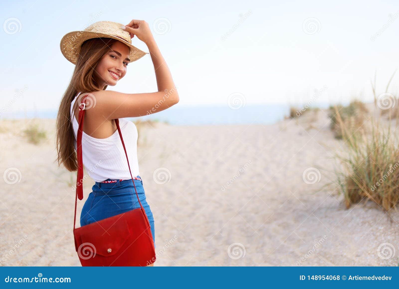 La Mujer Elegante Camina A La Playa En Sombrero De Paja Pantalones Cortos Del Dril De Algod N Del Verano Y Bolso De Moda Rojo He Foto De Archivo Imagen De Verano