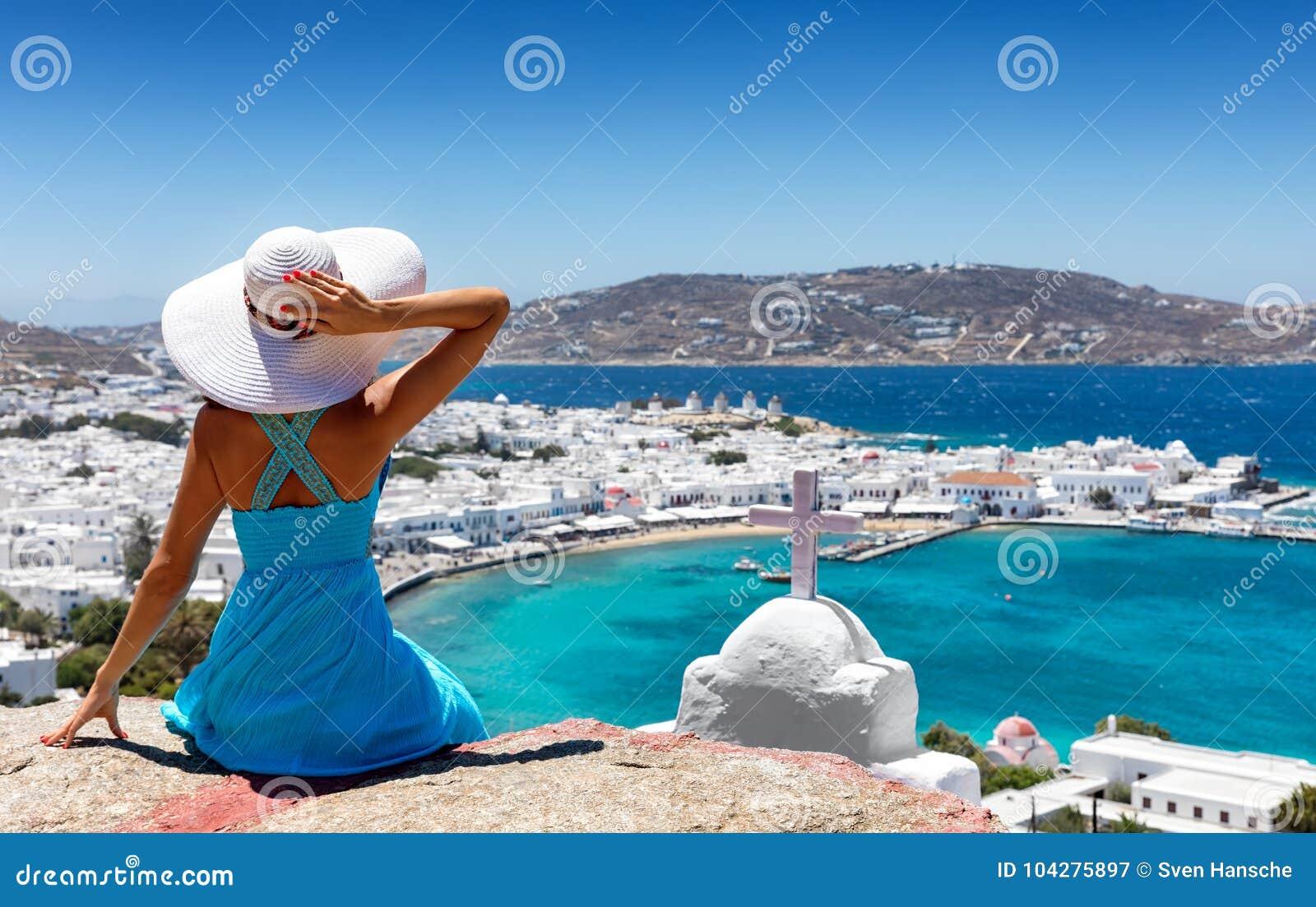 La mujer elegante disfruta de la visión sobre la ciudad de Mykonos