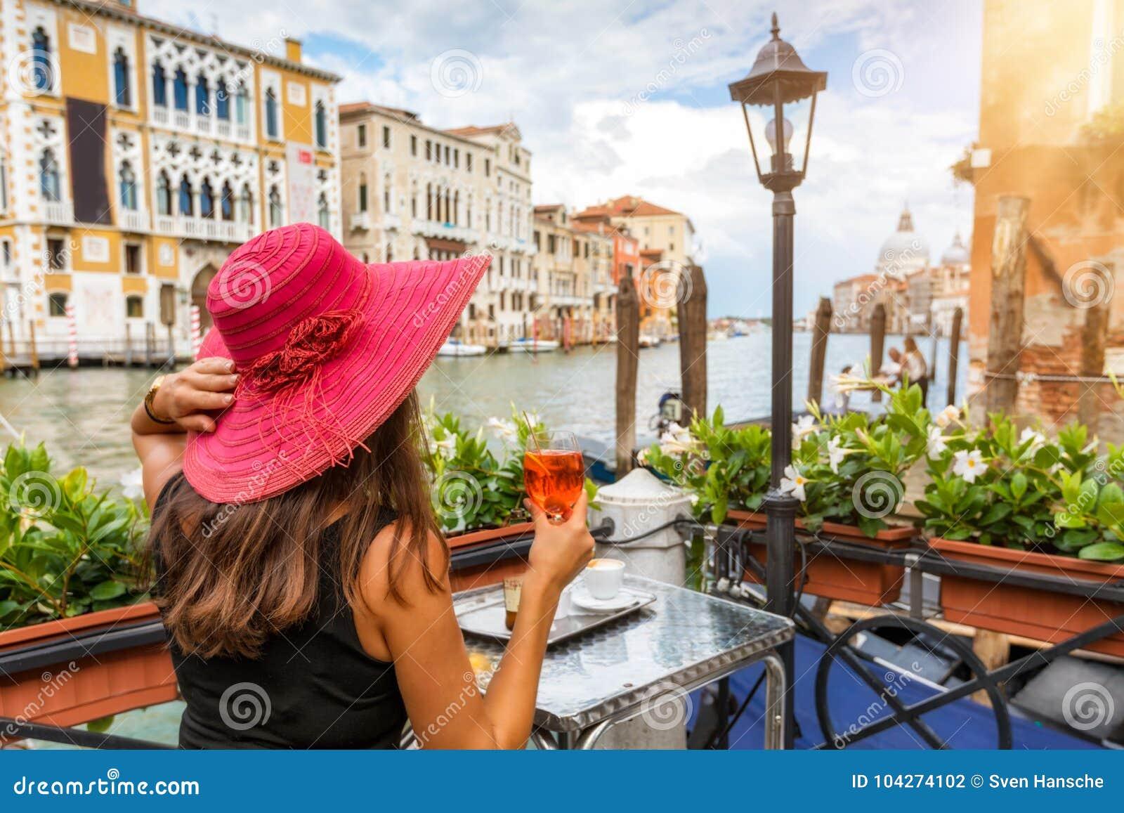 La mujer elegante goza de un aperitivo que se sienta al lado del Canale grande