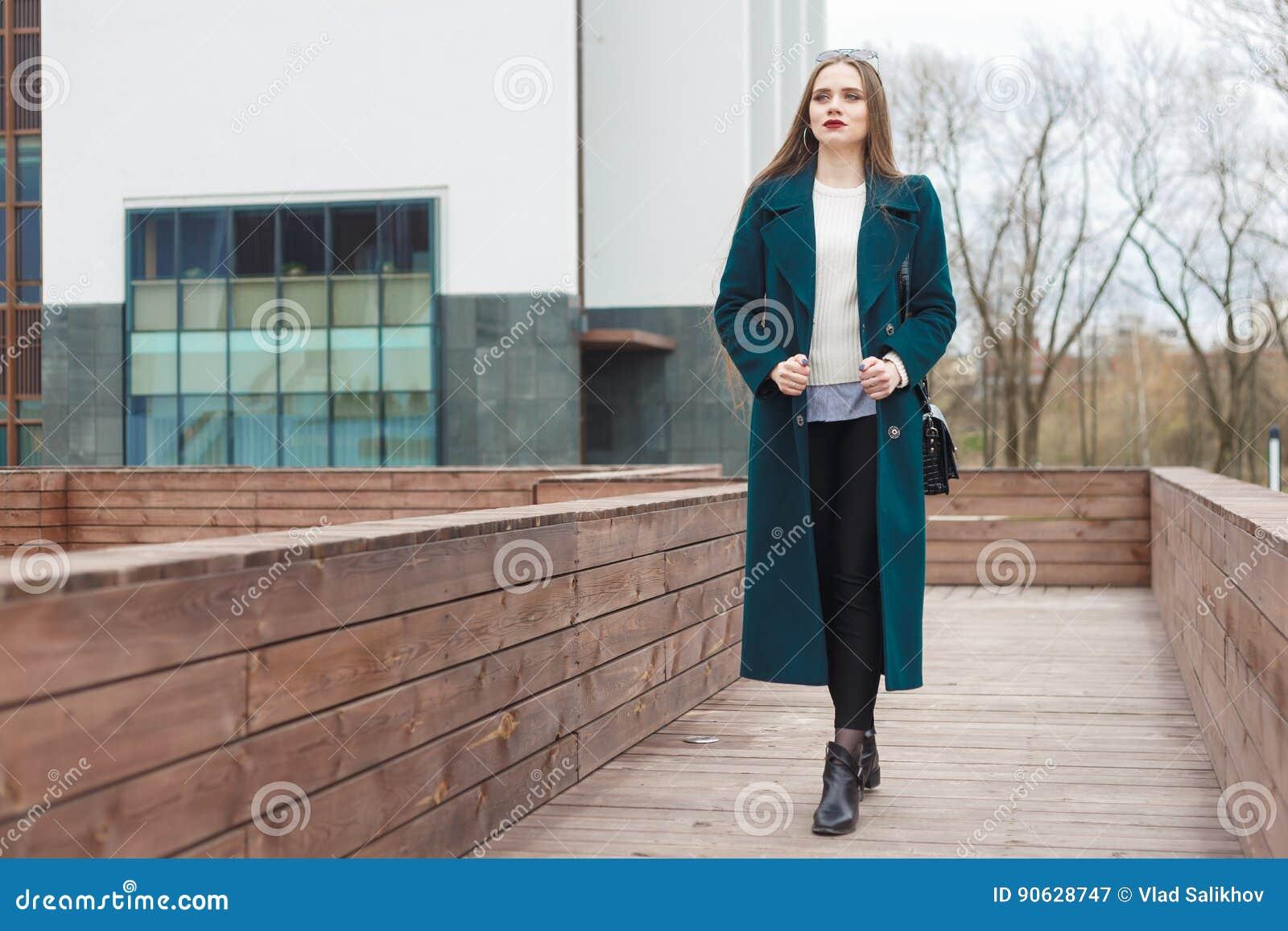 La mujer elegante hermosa joven que caminaba abajo de la calle en capa esmeralda y blanco hizo punto el suéter