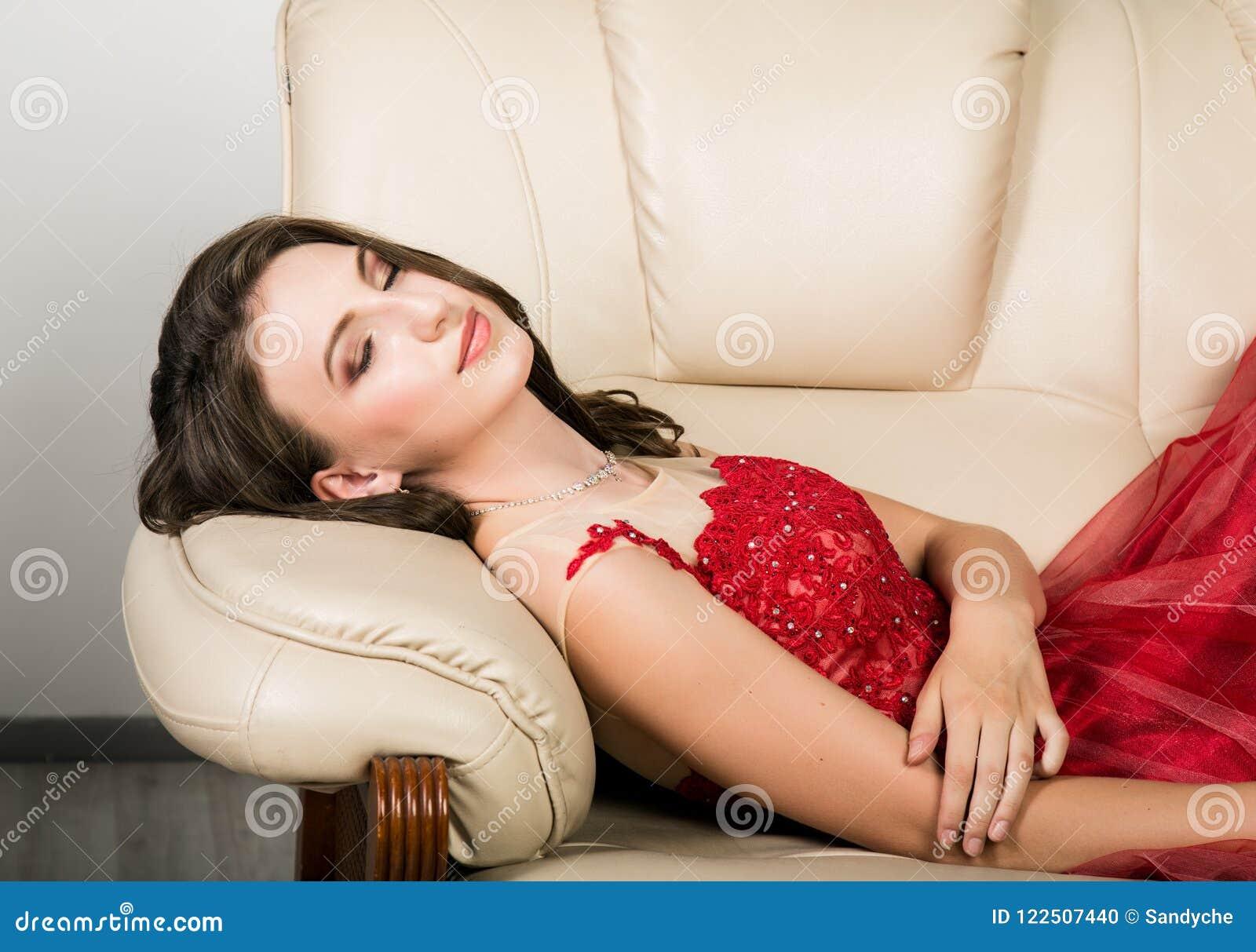 caf730917 La mujer elegante joven con el peinado profesional en vestido rojo largo  descansó sobre el sofá
