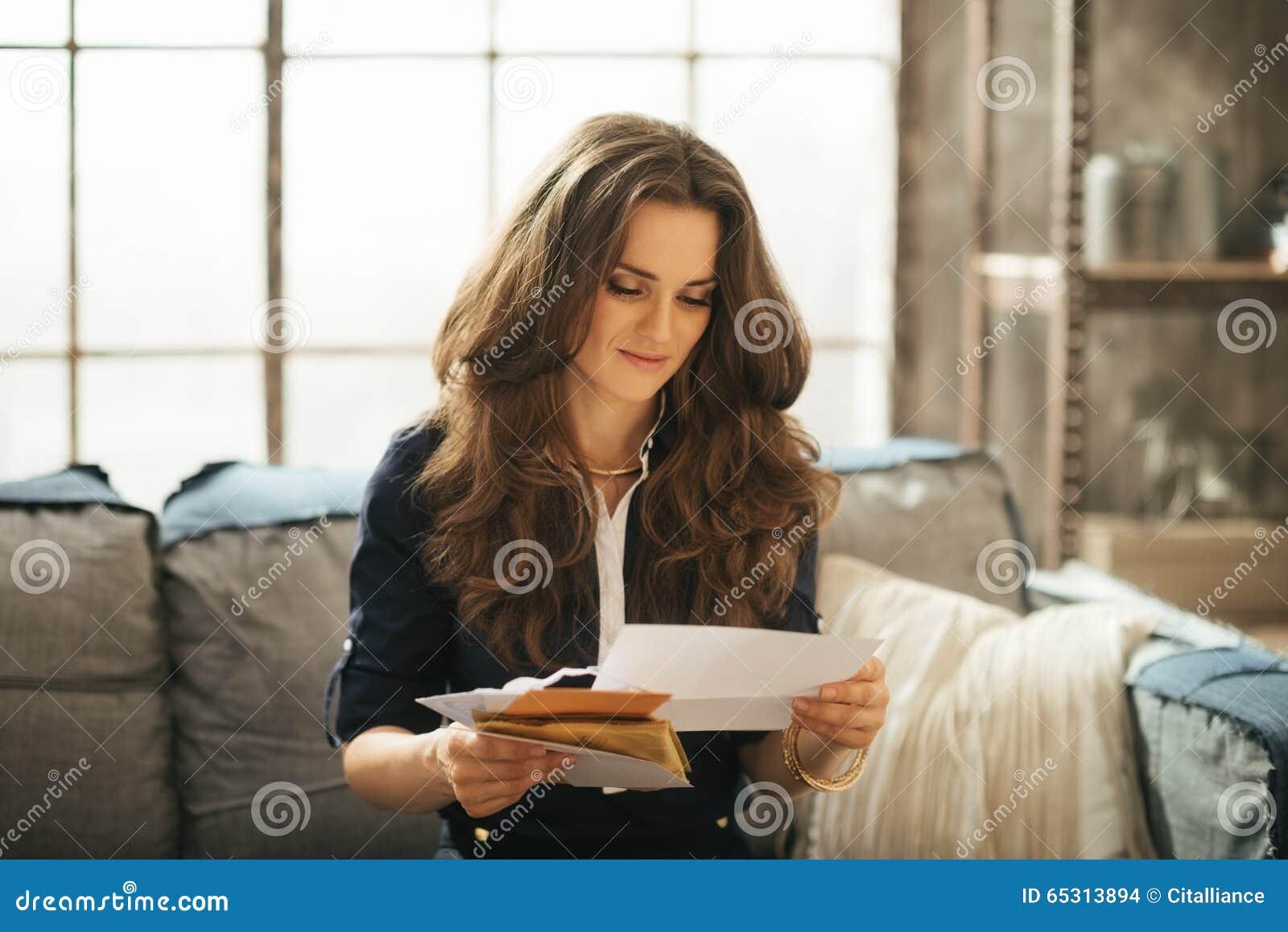 La mujer elegante se está sentando en el sofá y está leyendo correspondencia