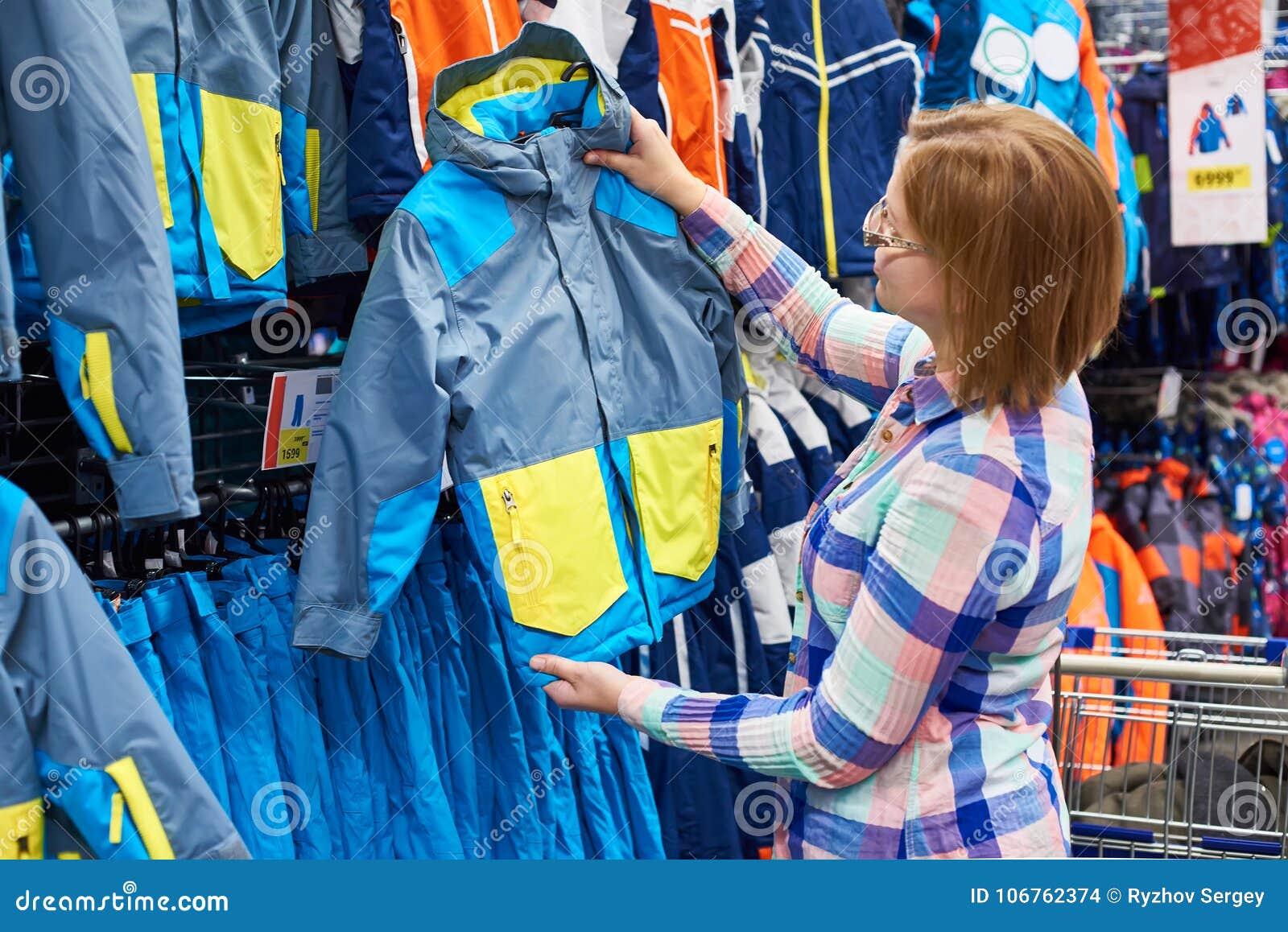 05de2473d65 La mujer elige la chaqueta del invierno de los niños en tienda del deporte