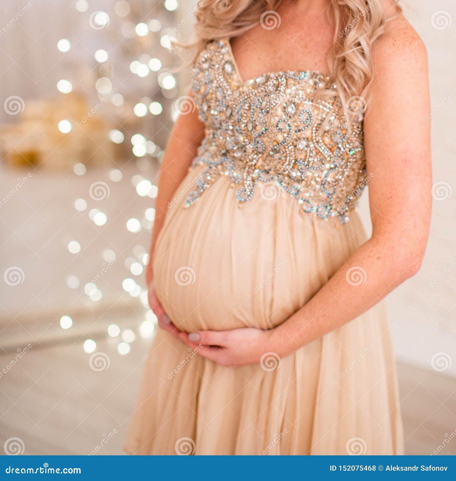 La mujer embarazada apoya un estómago grande con las manos en la parte inferior