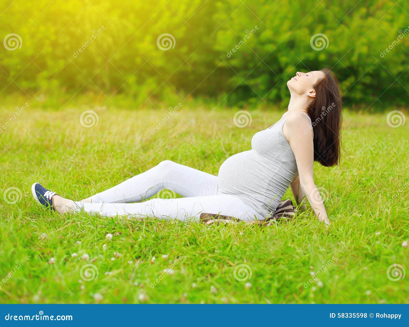 La mujer embarazada feliz que se sienta en la hierba y disfruta de verano