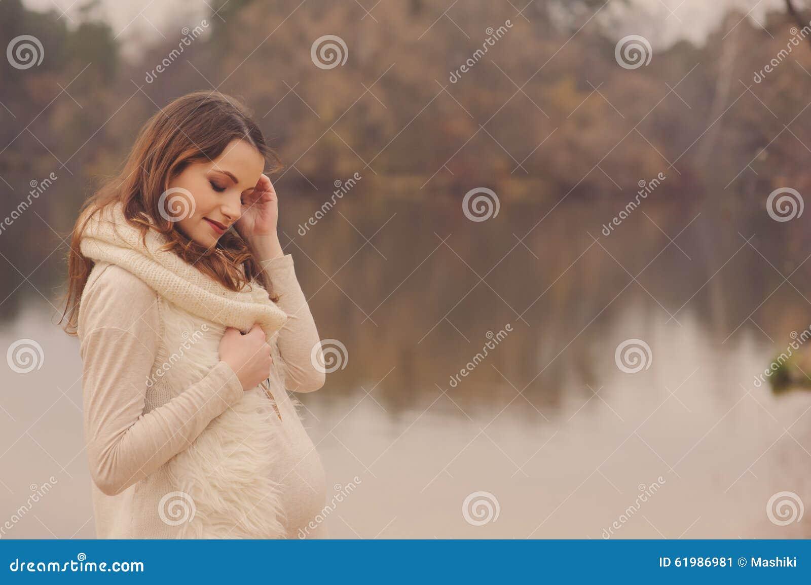 La mujer embarazada hermosa joven en acogedor calienta el paseo en la orilla del otoño, foco entonado, suave caliente