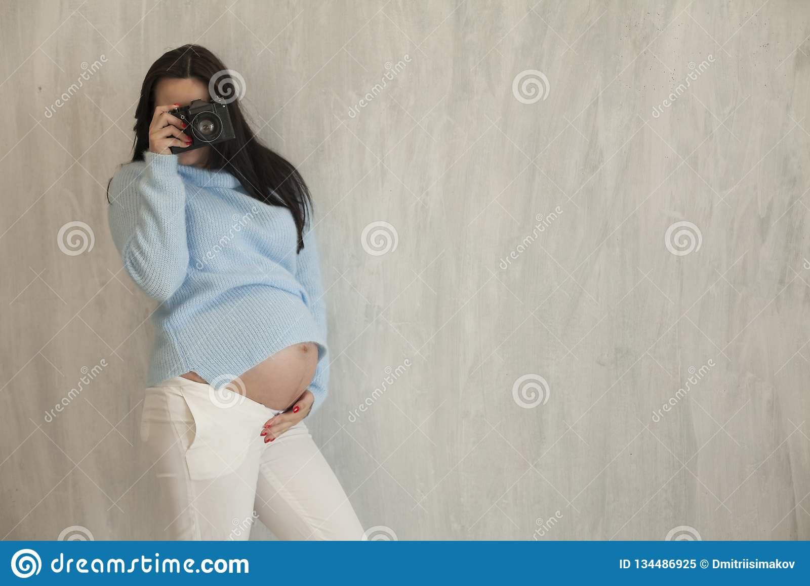 La mujer embarazada hermosa toma una imagen en la cámara